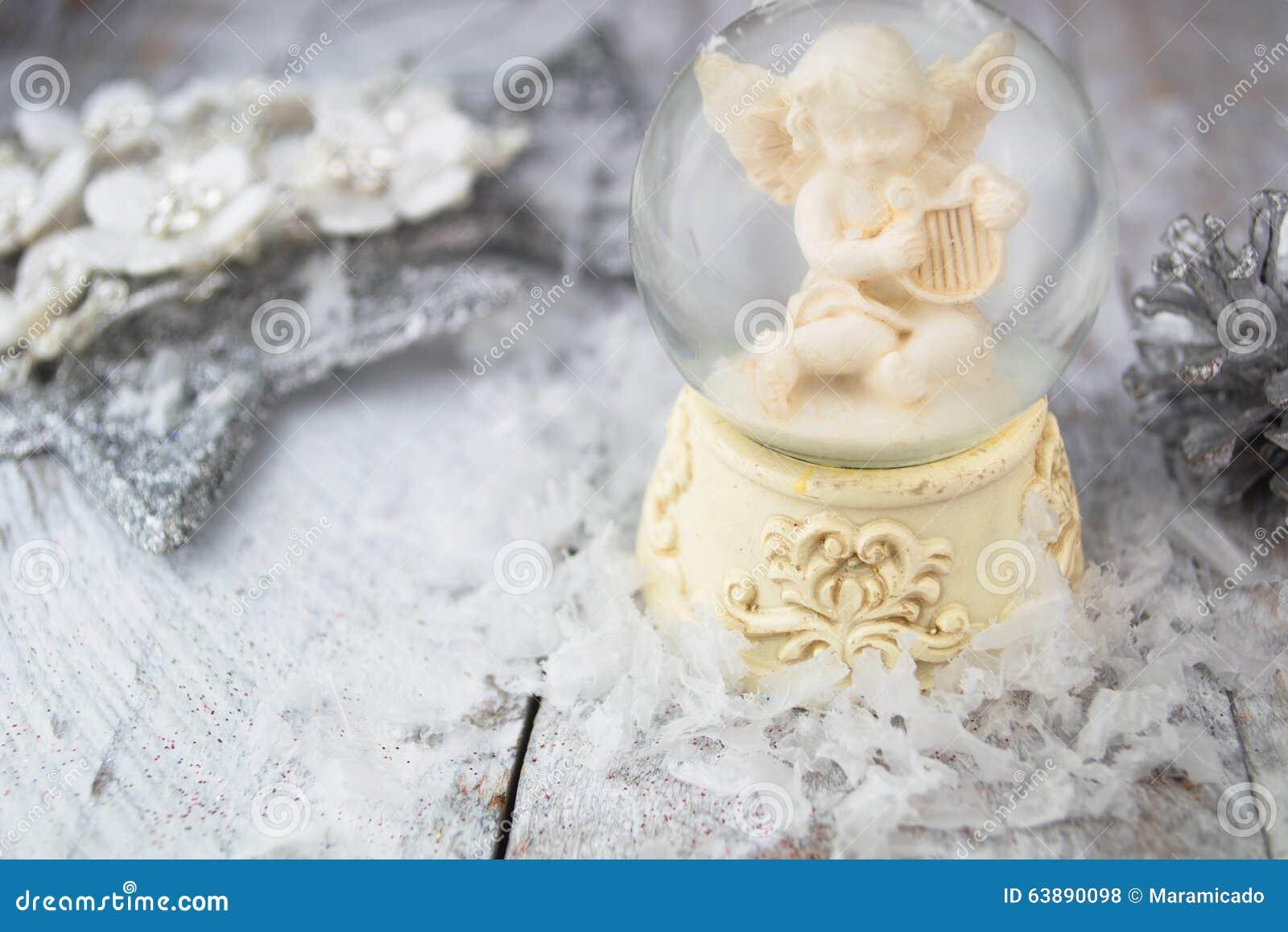 Het beeldje van de Kerstmisengel op zilveren achtergrond