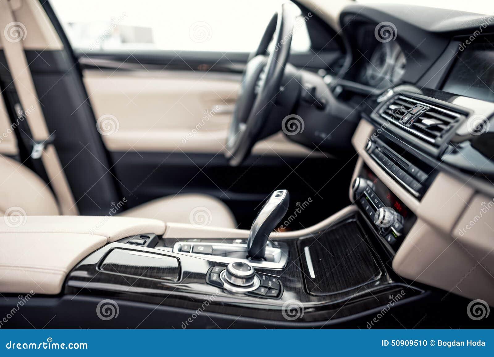 Het beige en zwarte binnenland van moderne auto, close-updetails van automatisch transmissie en toestel plakt tegen stuurwielbede