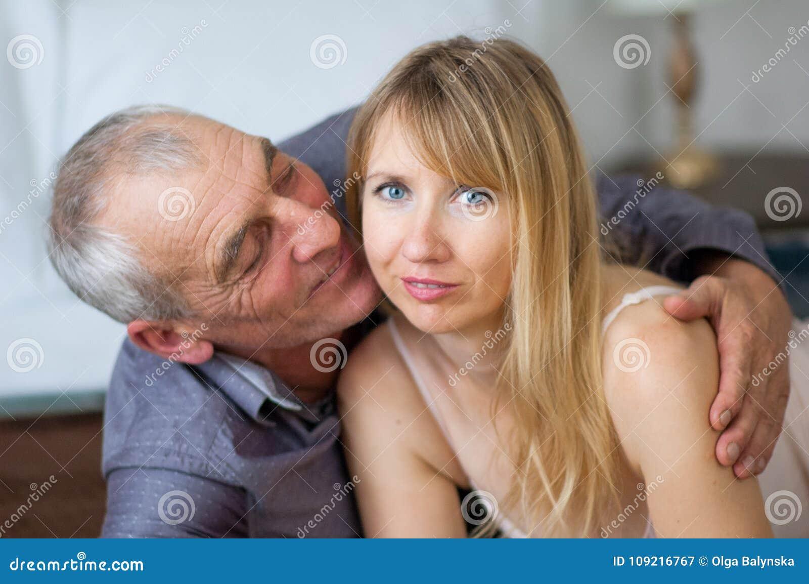 Het bejaarde omhelst en kust zijn Jonge Vrouw in Sexy Lingerie die in Bed in Hun Huis liggen Paar met Leeftijd