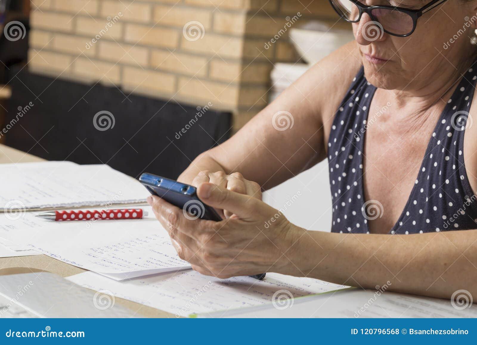 Het bekijken de mobiele telefoon op de het werklijst