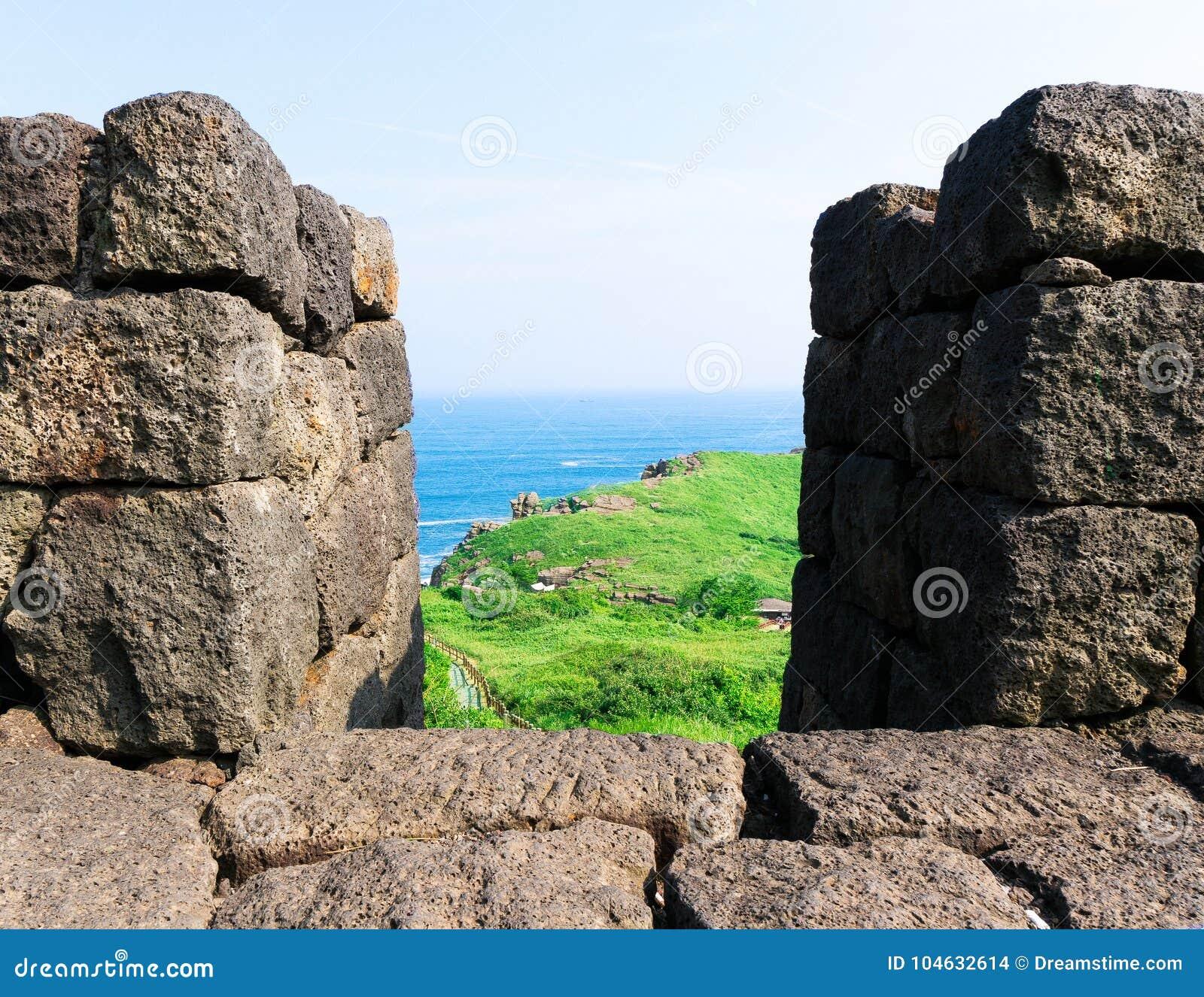 Download Het Bekijken Door Vulkanische Steenpijlers Groene Gras En Oceanen Stock Foto - Afbeelding bestaande uit hemel, rots: 104632614