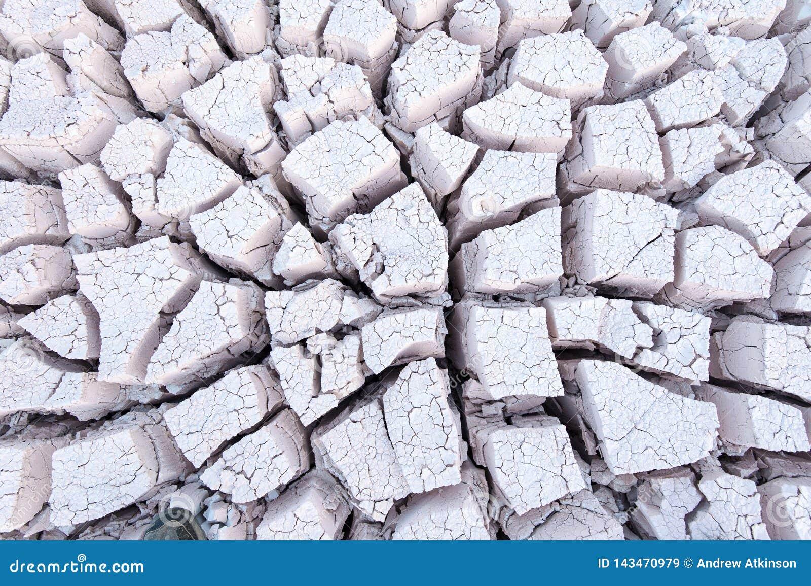Het bekijken neer op droge gebarsten grijze witte modder die patronen vormen de bodem van een rivierbed
