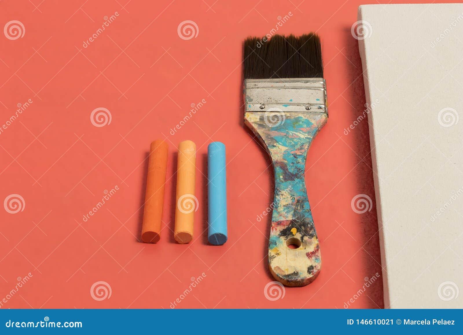 Het bevlekte penseel met blauwe en beige kleuren leeft van de koraalkleur wit canvas als achtergrond en oranje blauwe pastelkleur