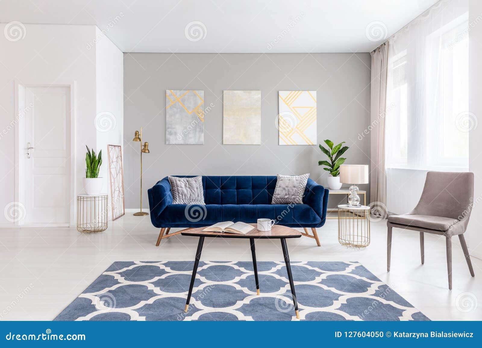 Het binnenland van de open plekwoonkamer met modern binnen meubilair van een marineblauwe sofa, een beige leunstoel, een koffieta