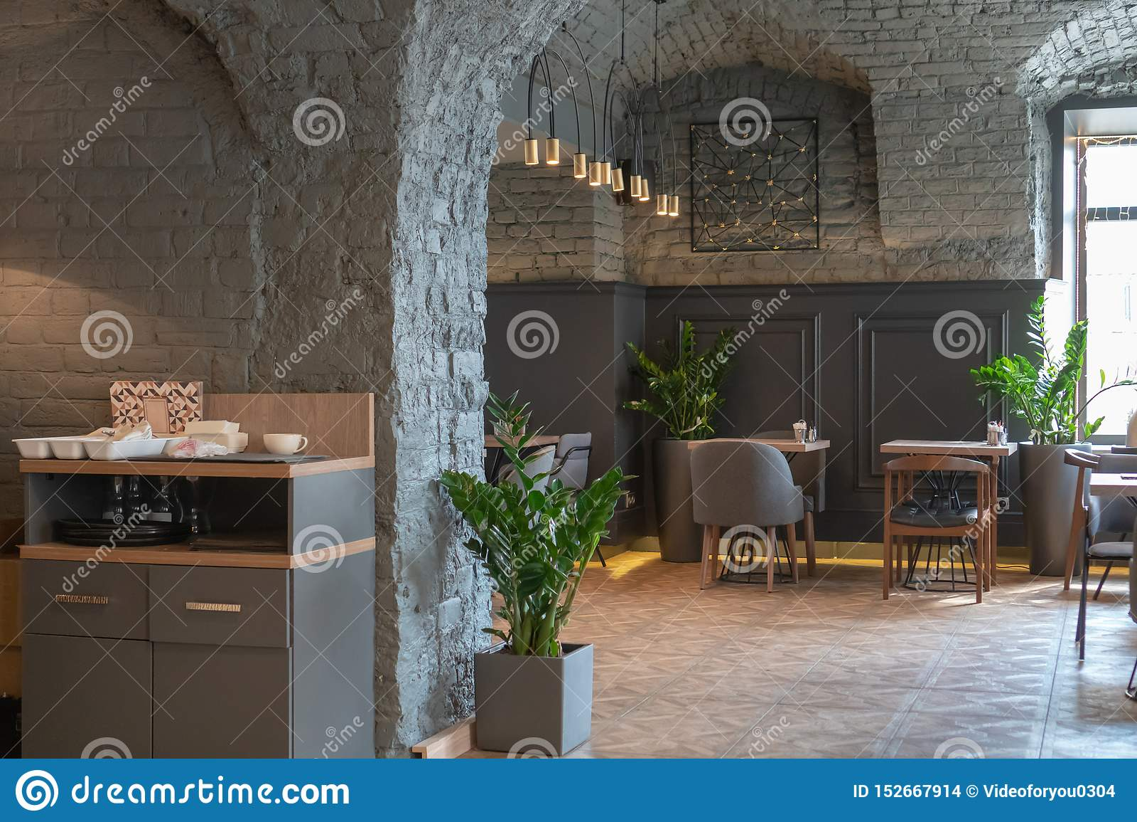 Het binnenland van een comfortabel restaurant in de zolderstijl Modieuze koffie met een baksteen grijze muur