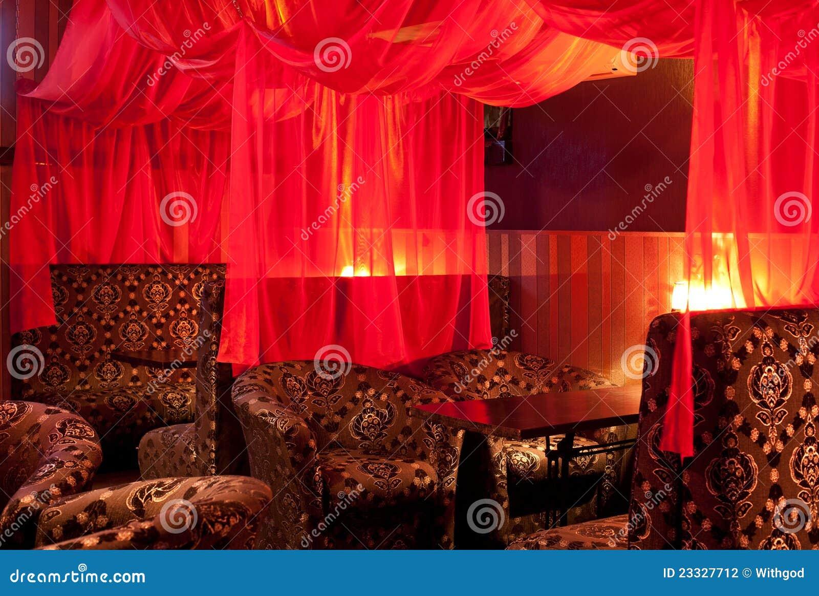 het binnenland van het restaurant oosterse stijl zachte banken en rode transparante gordijnen