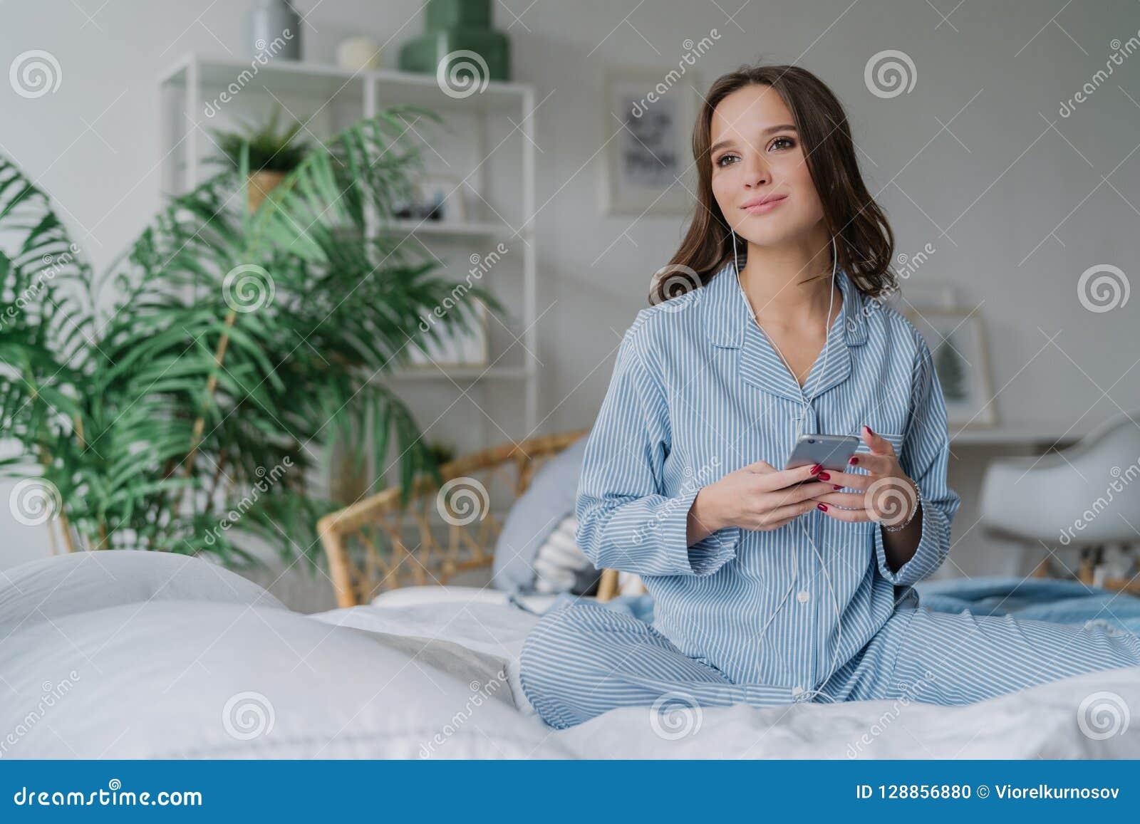 Het binnenschot van mooie jonge vrouw let op favoriete serie met oortelefoons en de slimme telefoon, downloadt nieuwe liederen, p