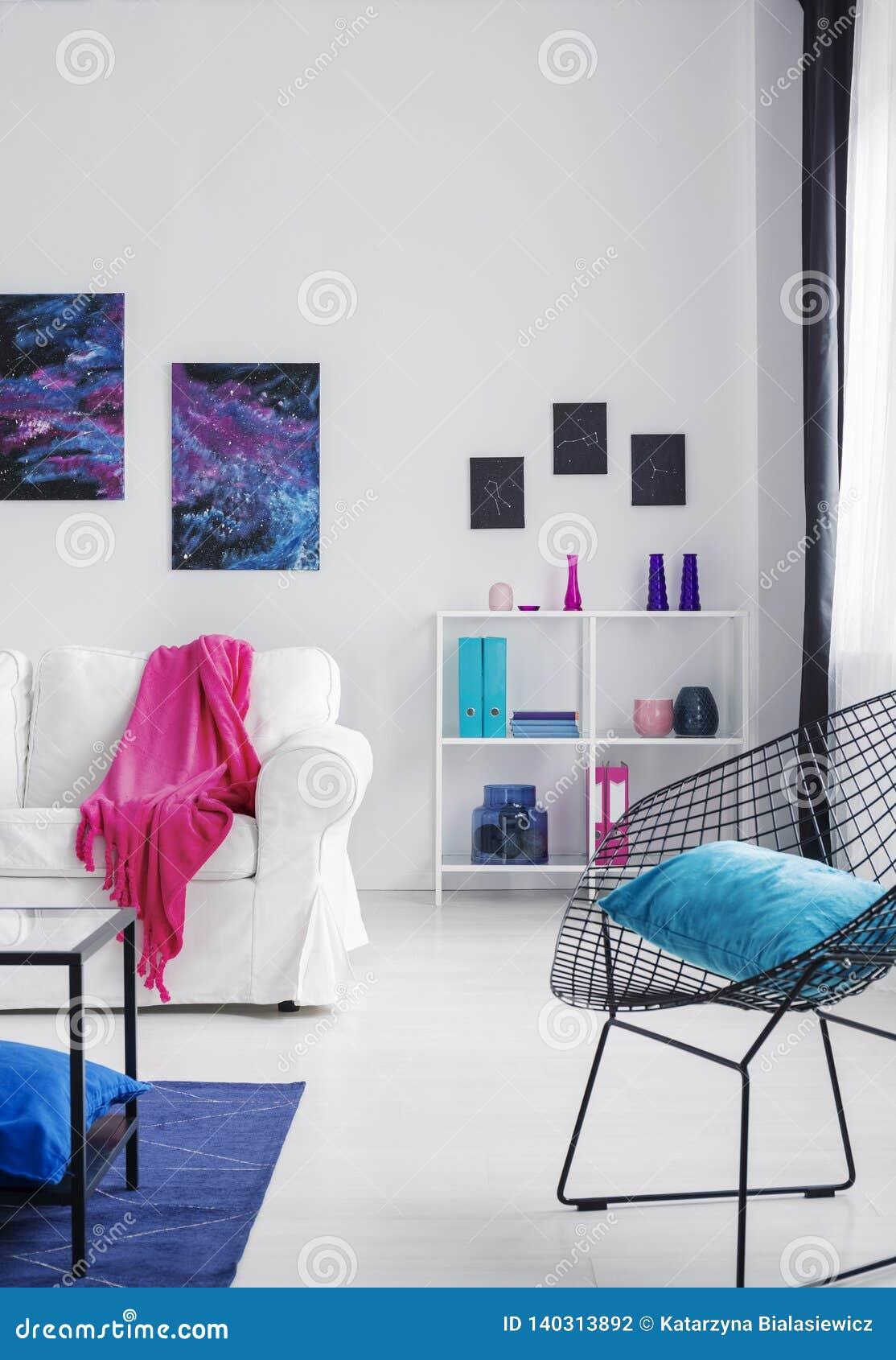 Het blauwe hoofdkussen op zwarte modieuze metaalleunstoel in heldere kosmos inspireerde binnenland met wit meubilair, echte foto