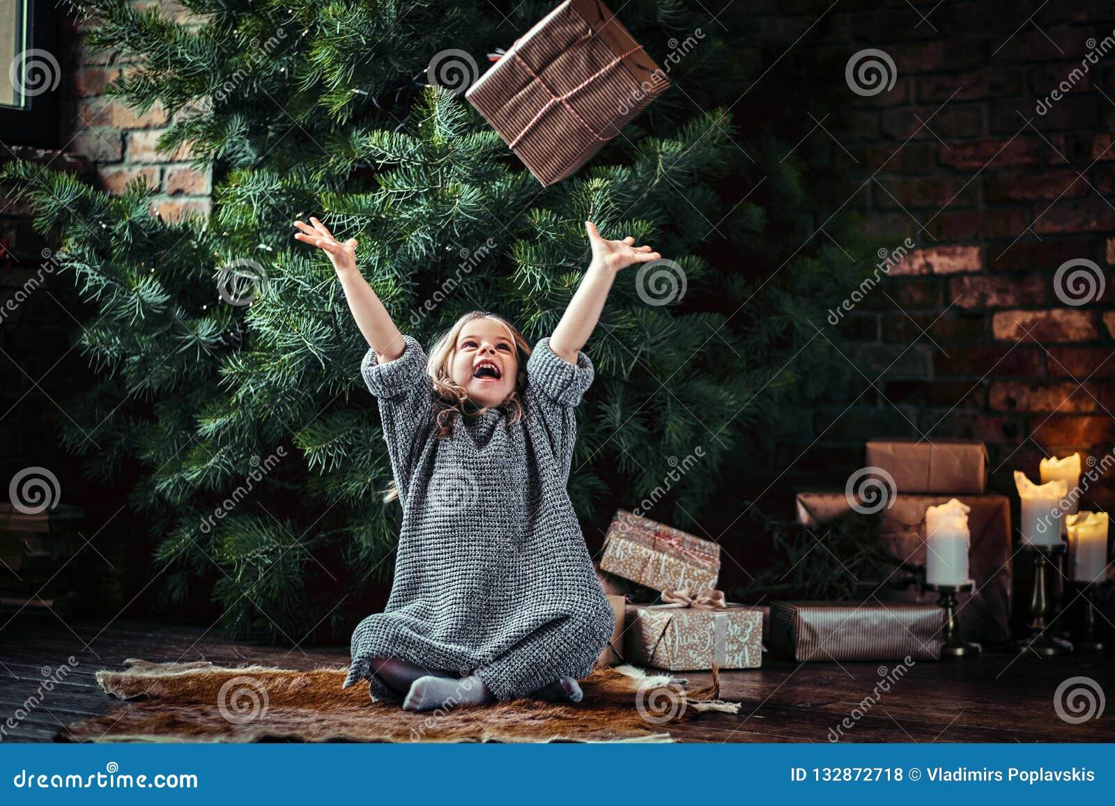 Het blije meisje met blonde krullend haar die een warme sweater dragen werpt op een giftdoos terwijl het zitten op een vloer naas