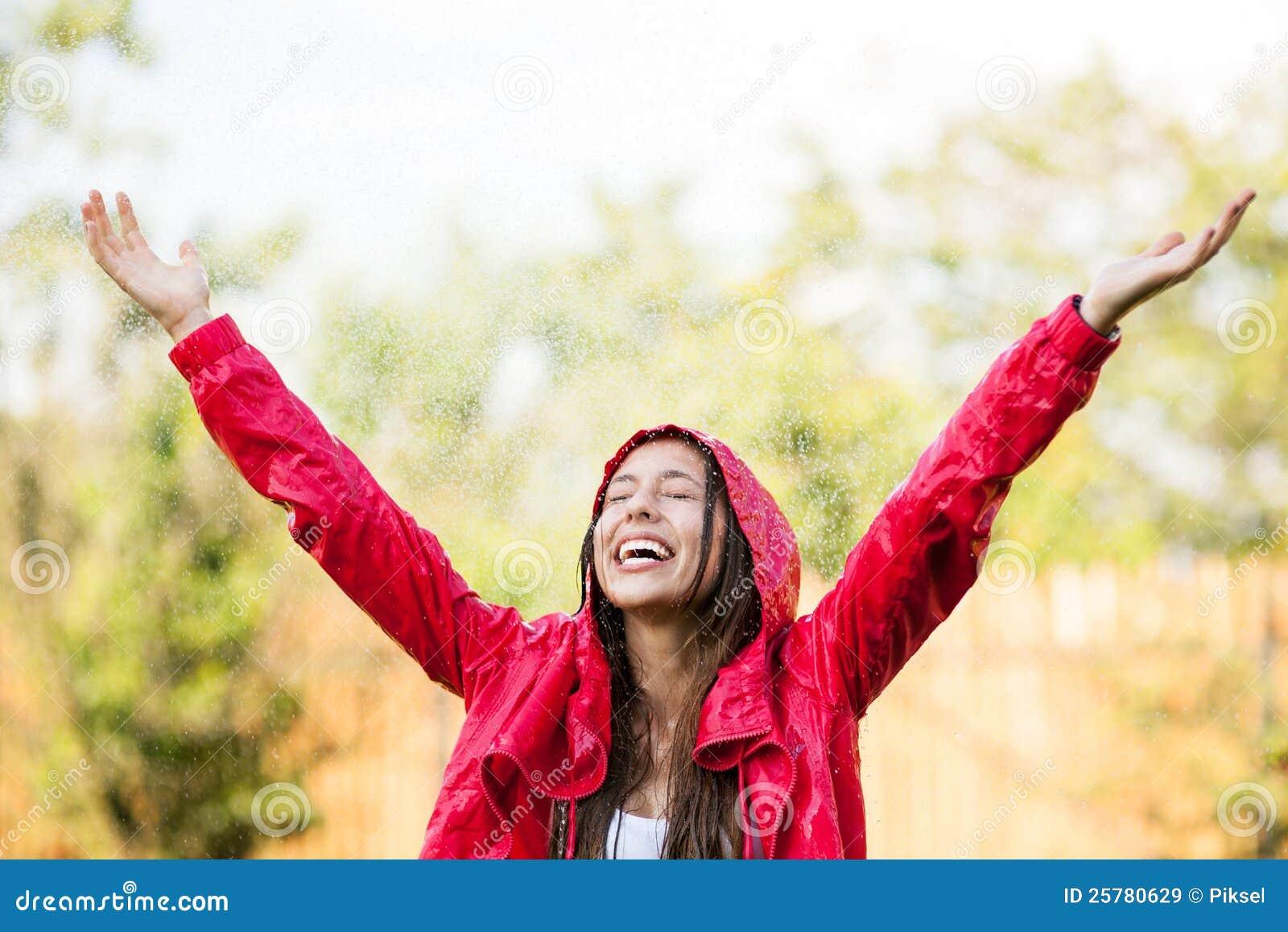 Het blije vrouw spelen in regen
