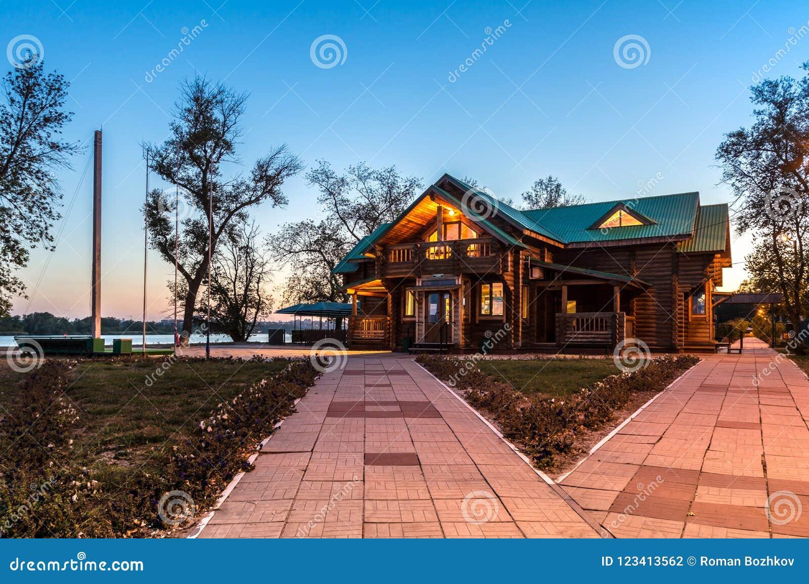 Het blokhuis van het land met verlichting en groen dak op de achtergrond van de avond blauwe hemel