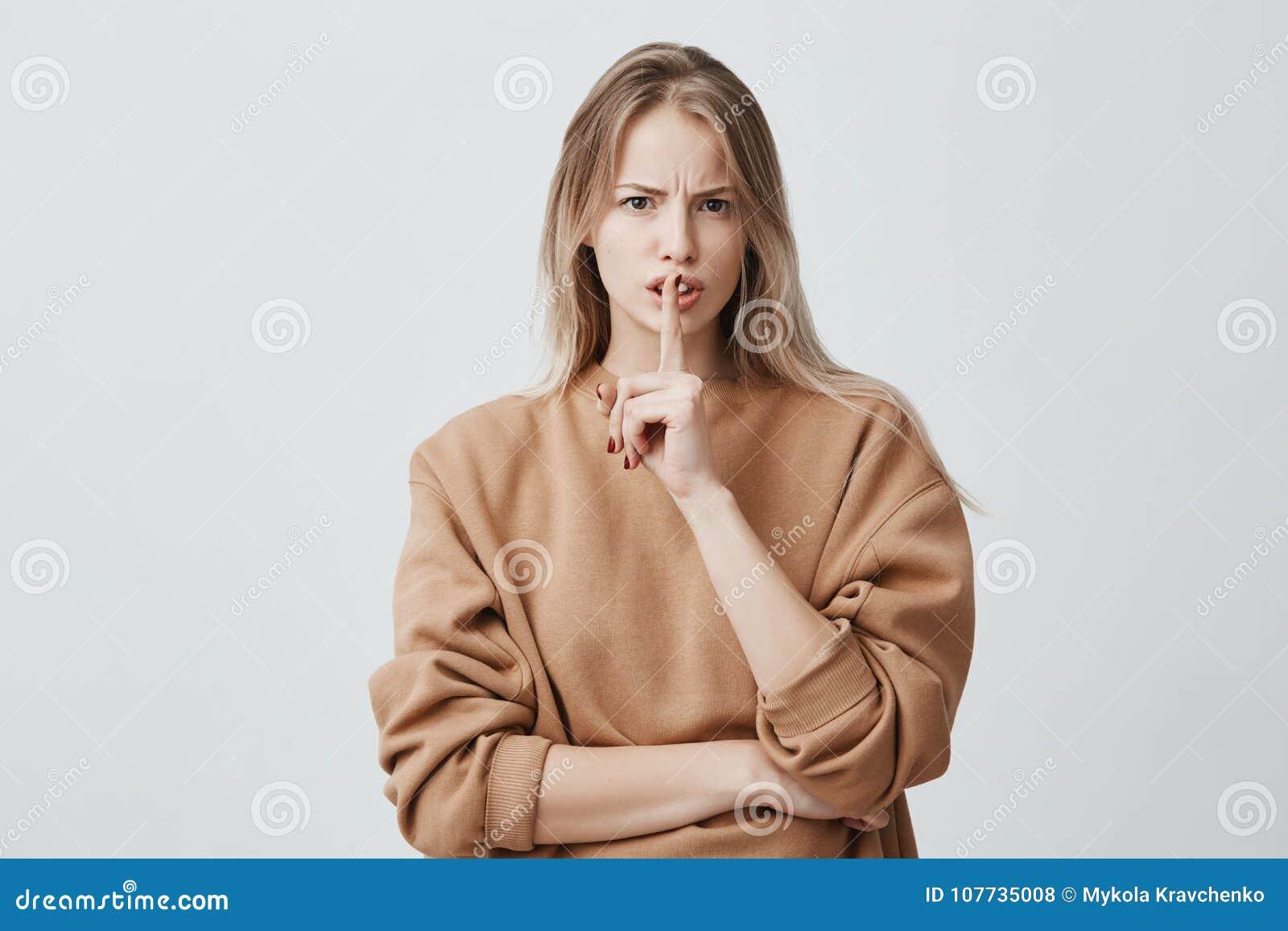Het blonde het aantrekkelijke Europese wijfje camera bekijkt houdt vinger op lippen die, en vraagt om lawaai niet te maken zijn n