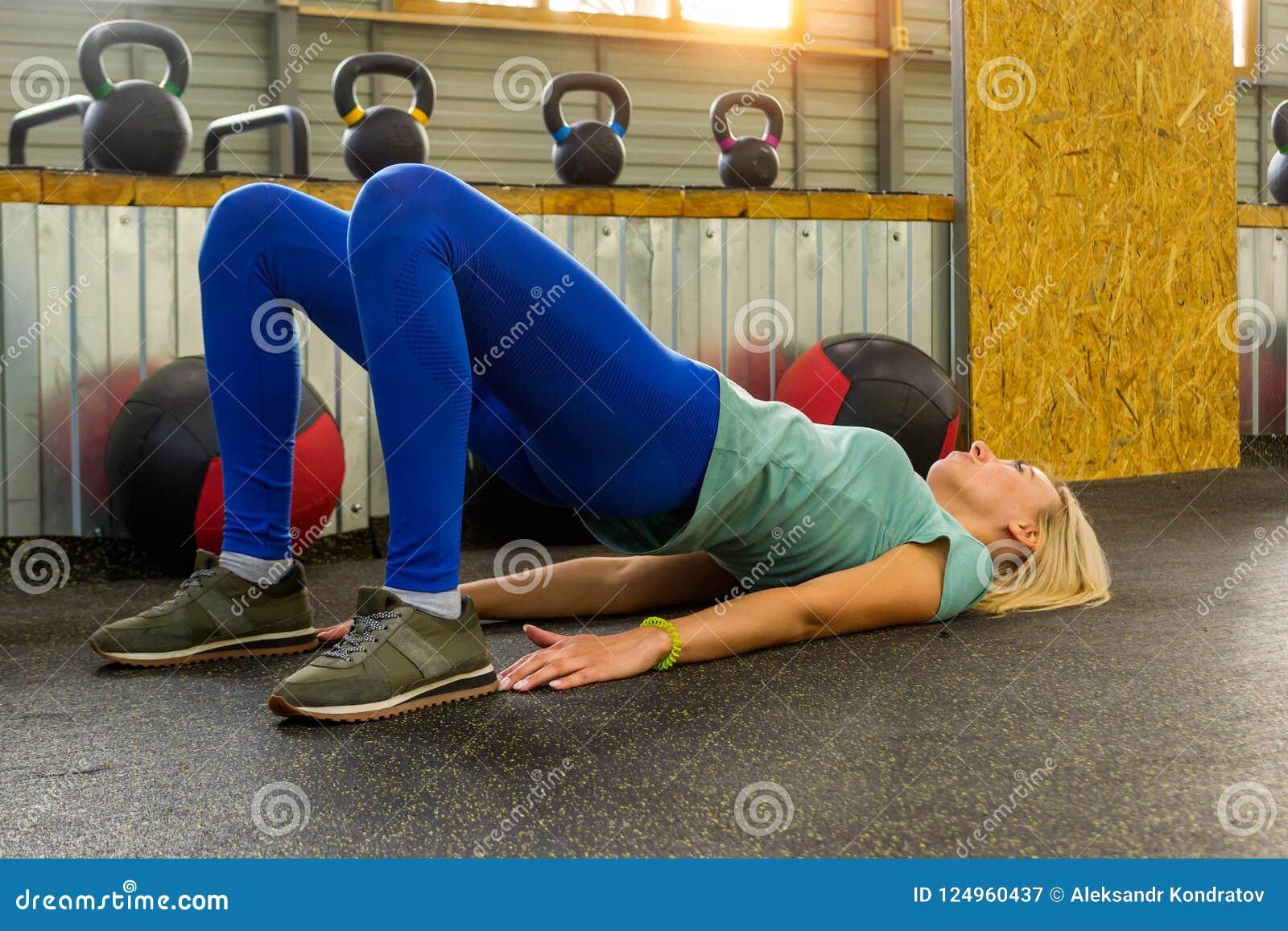 Het blonde beatifullmeisje maakt een opwarming liggend op de vloer in t