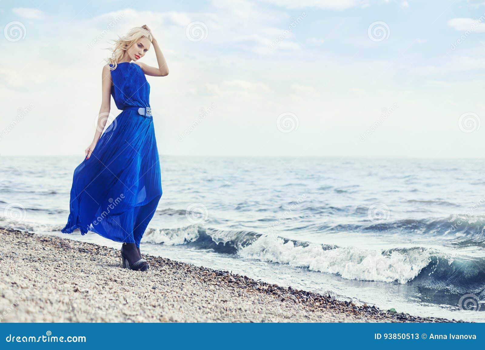 Het blonde in blauwe kleding loopt op zee langs de promenade door overzees, de zomervakantie Mooi sensueel portret van een geheim