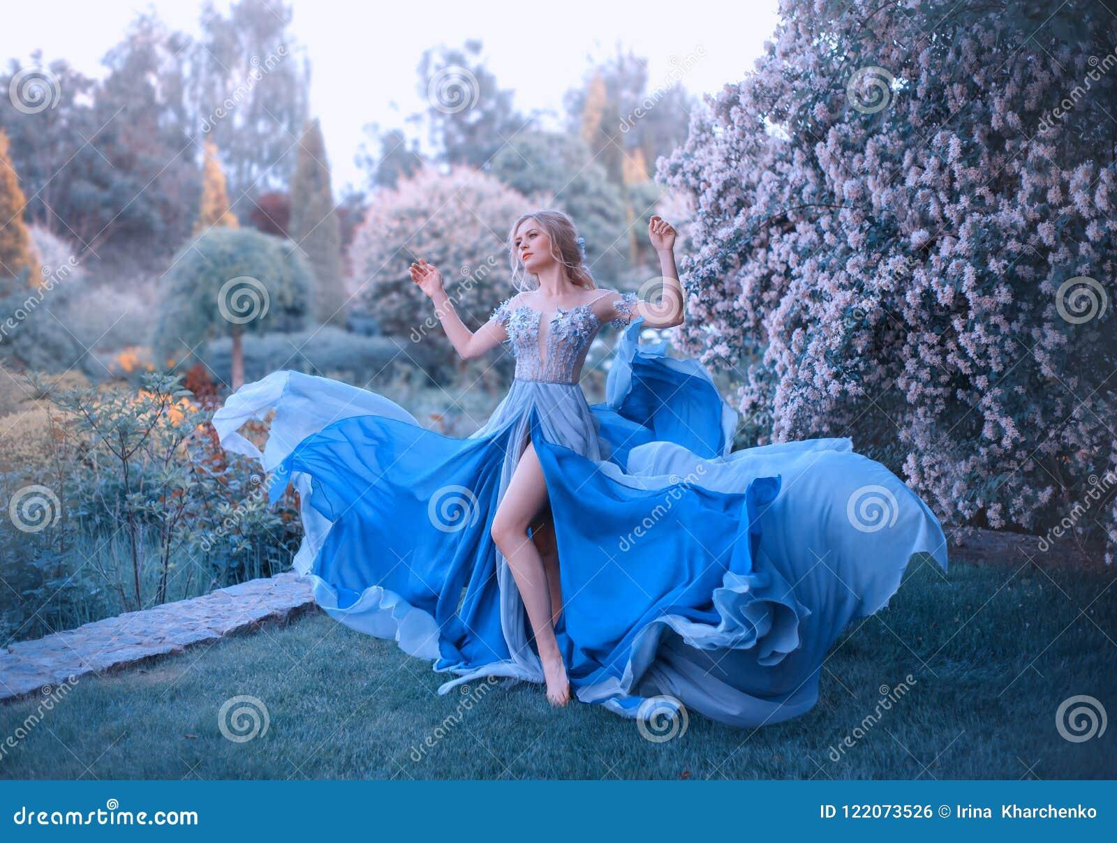 Het blonde, met een mooi elegant kapsel, loopt in een fabelachtige bloeiende tuin Prinses in een lange grijs-blauwe kleding met a