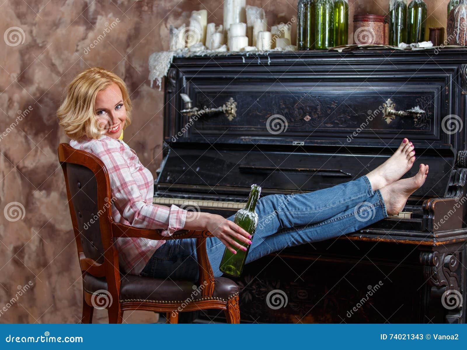 Het blonde vrouw stellen dichtbij retro piano met in de was gezette wijnfles