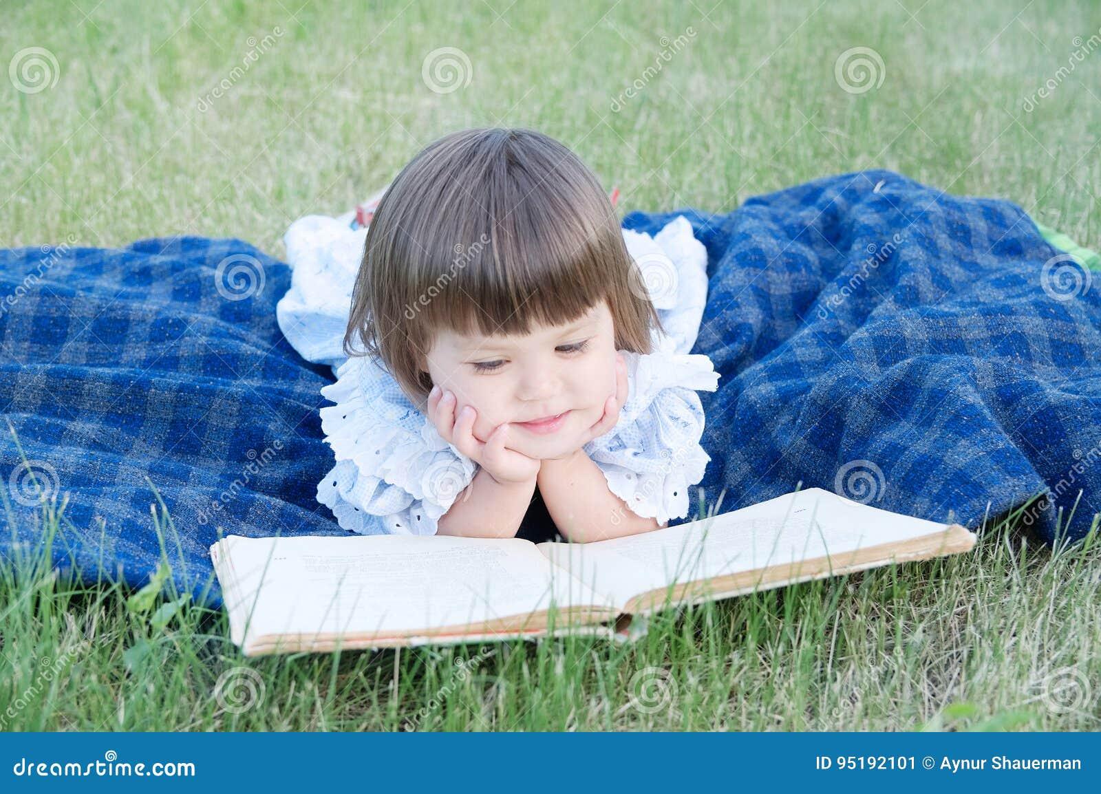 Het boek die van de meisjelezing bij maag openlucht, glimlachend leuk kind, kinderenonderwijs en de ontwikkeling liggen Jonge gei