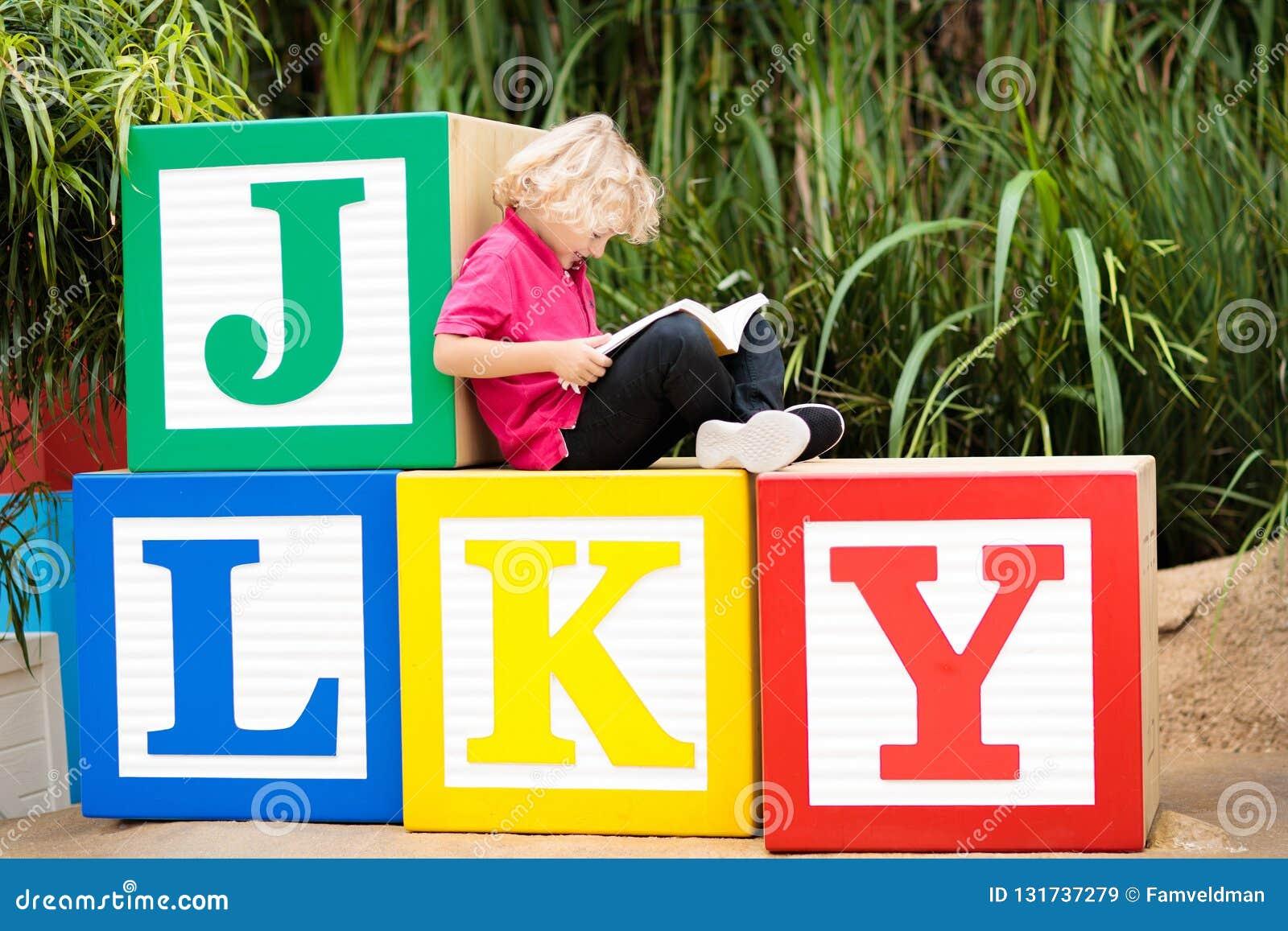 Het boek van de kindlezing in schoolyard Jong geitje het leren abc brieven Weinig jongenszitting op houten stuk speelgoed blokken