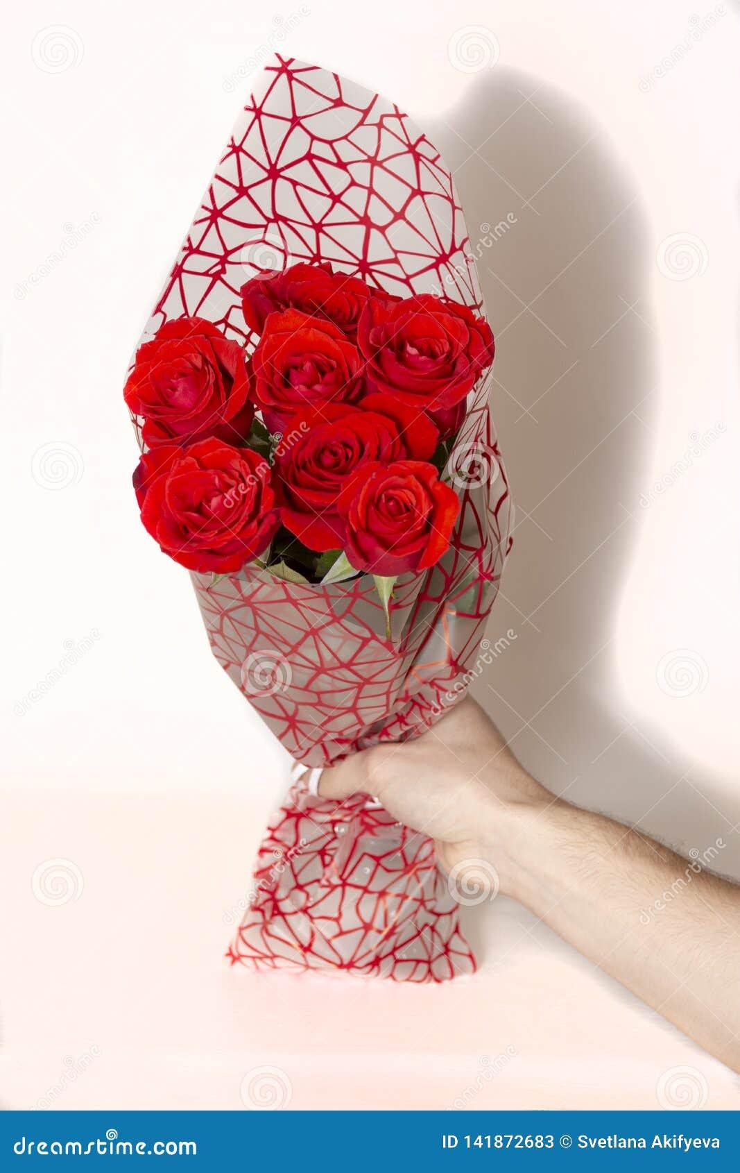Het boeket van de handholding van rode rozen over witte achtergrond