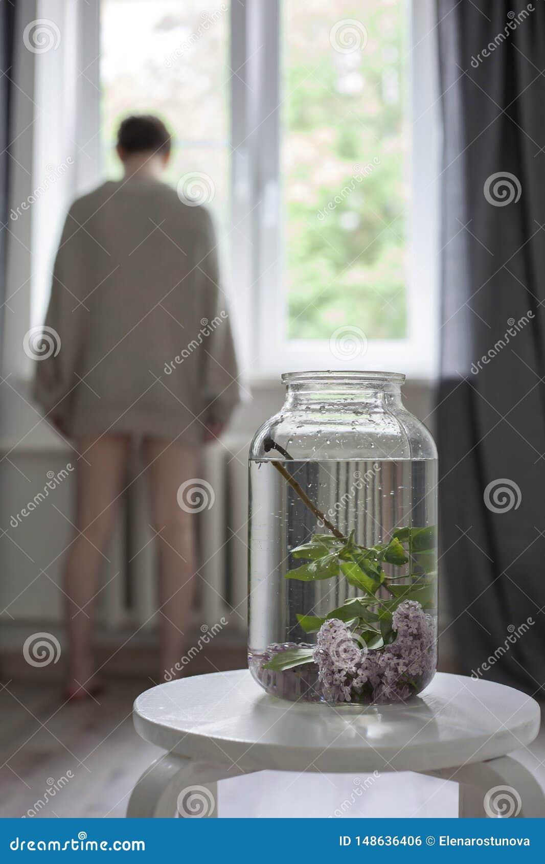 Het boeket van lilac takjes in een transparante groene kruik op de witte stoel als decoratie van binnenland
