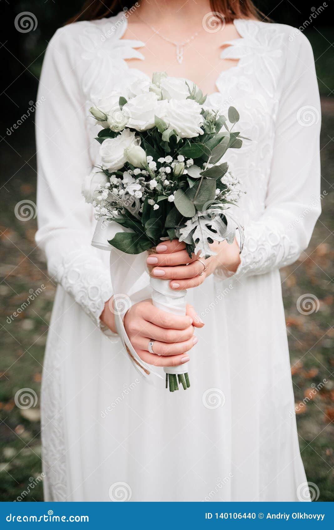 Het boeket van het schoonheidshuwelijk van roze bloemen en eucalyptustakken in de handen van de bruid