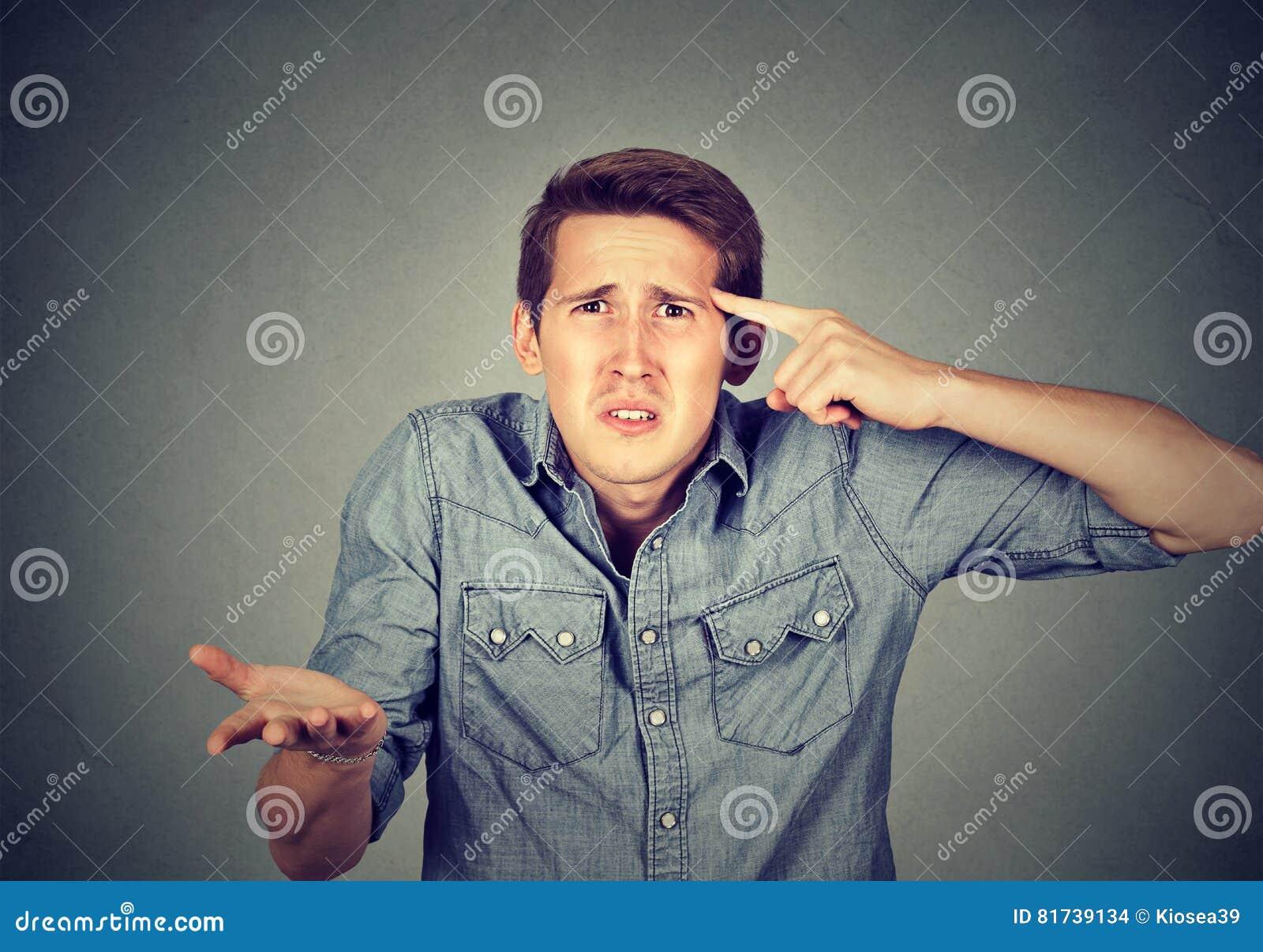 Het boze mens gesturing met zijn vinger tegen tempel is gek u?