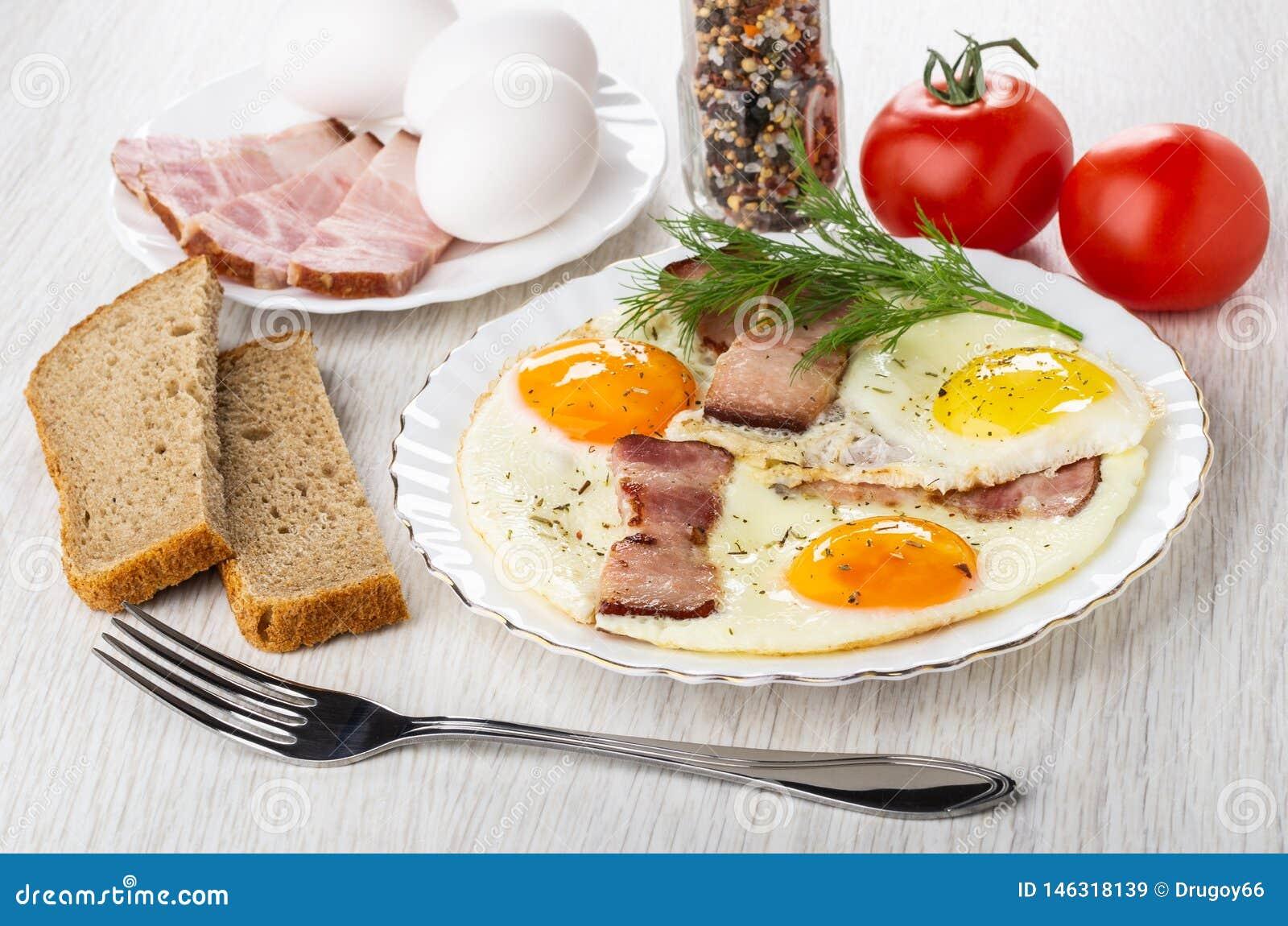 Het brood, tomaten, specerij, braadde eieren met borststuk en dille in plaat, vork op lijst