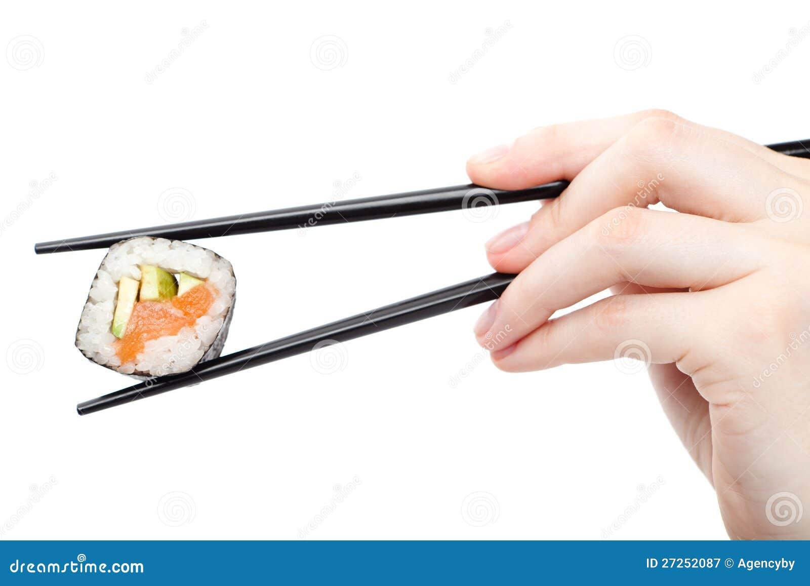 Het broodje van de holdingssushi van de hand met zwarte eetstokjes