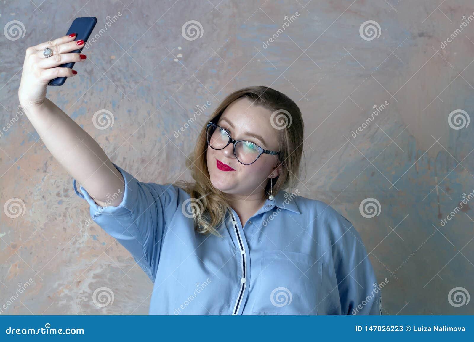 Het bruin-haired meisje maakt selfie met de telefoon