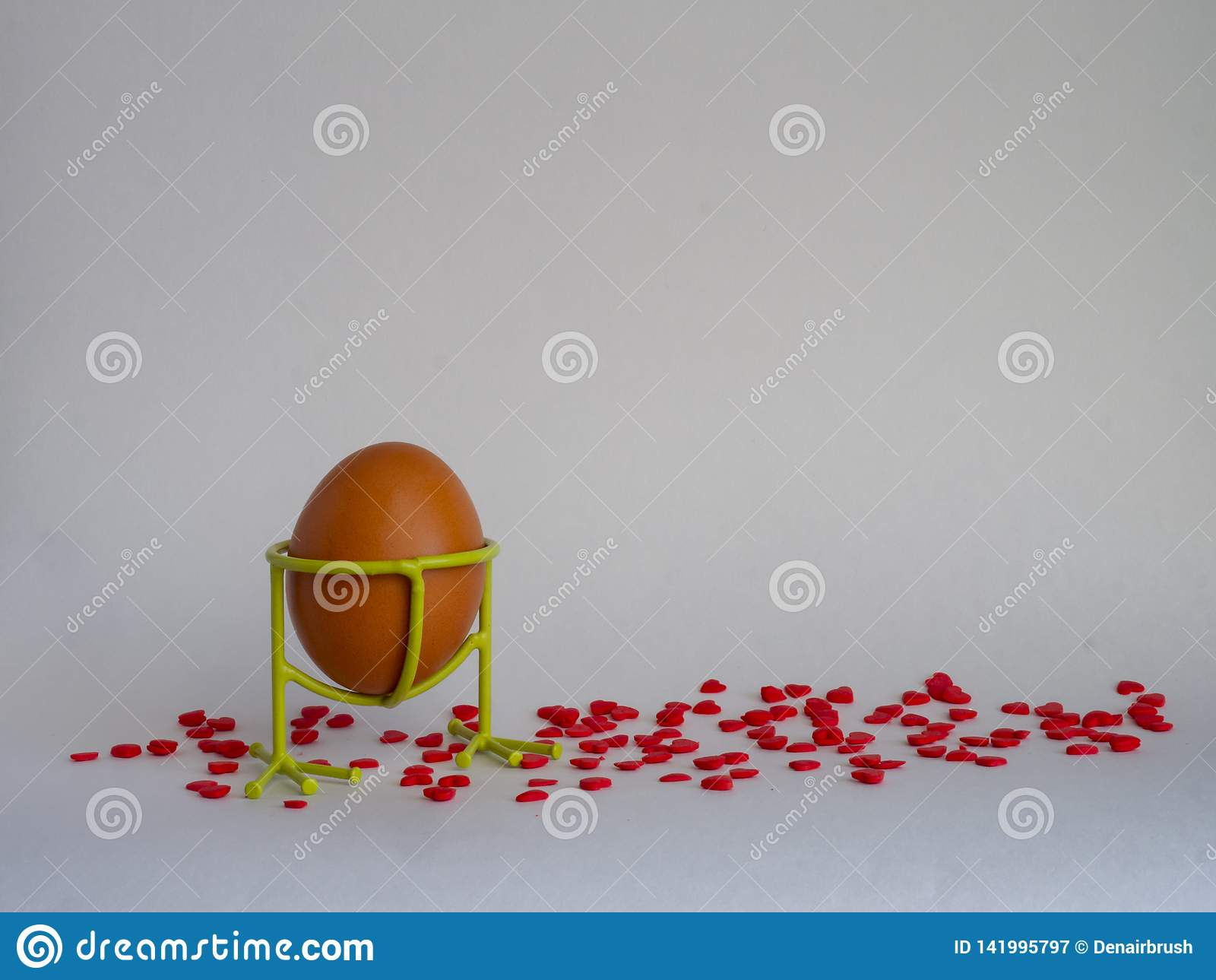 Het bruine ei van lichte kleur in een steun treft voor de vakantie Pasen op een witte die achtergrond voorbereidingen met helder