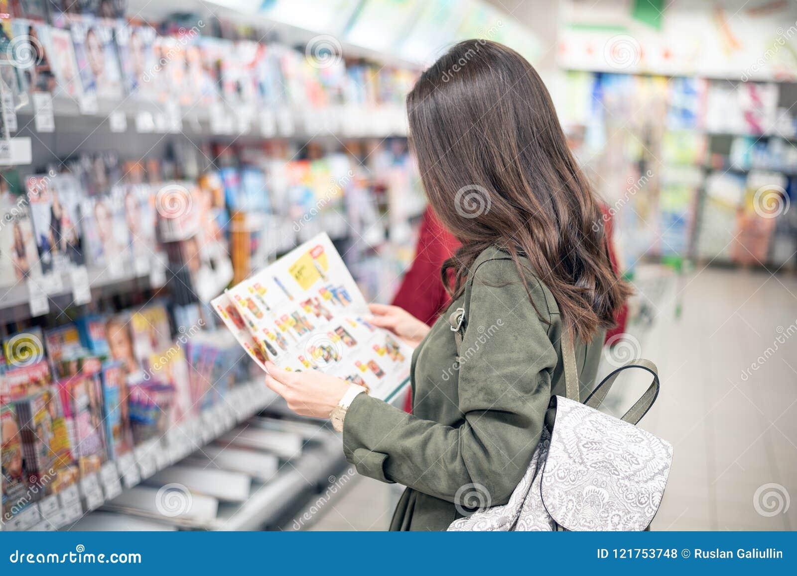 Het brunette bevindt zich in de Wandelgalerij dichtbij de tijdschriftplanken en bekijkt de productcatalogus