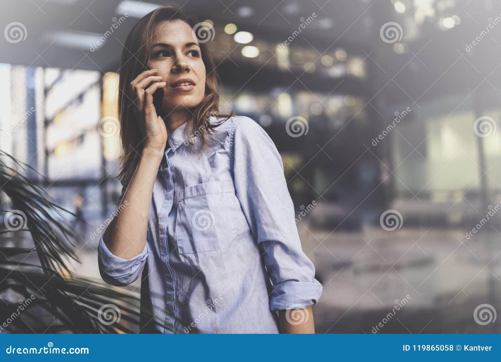 Het charmante jonge bedrijfsvrouw spreken met partner via mobiele telefoon terwijl status op modern commercieel centrum