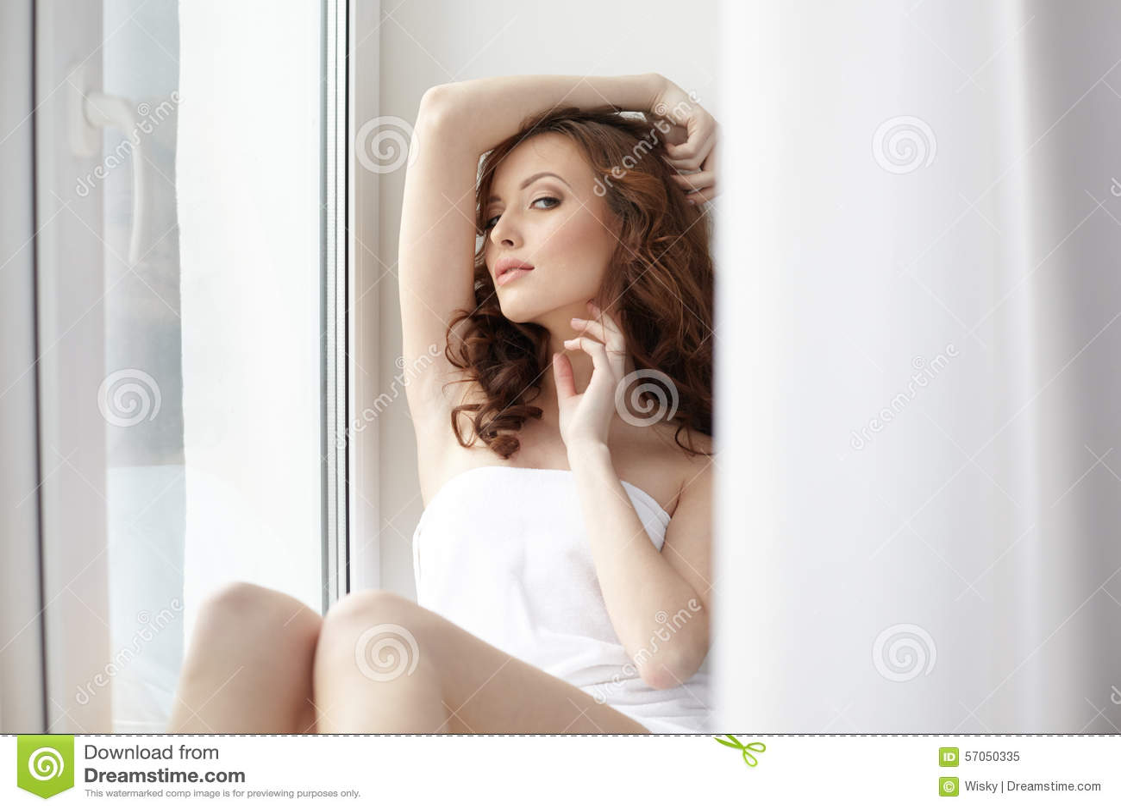 Het charmante vrouw stellende doen leunen op vensterbank