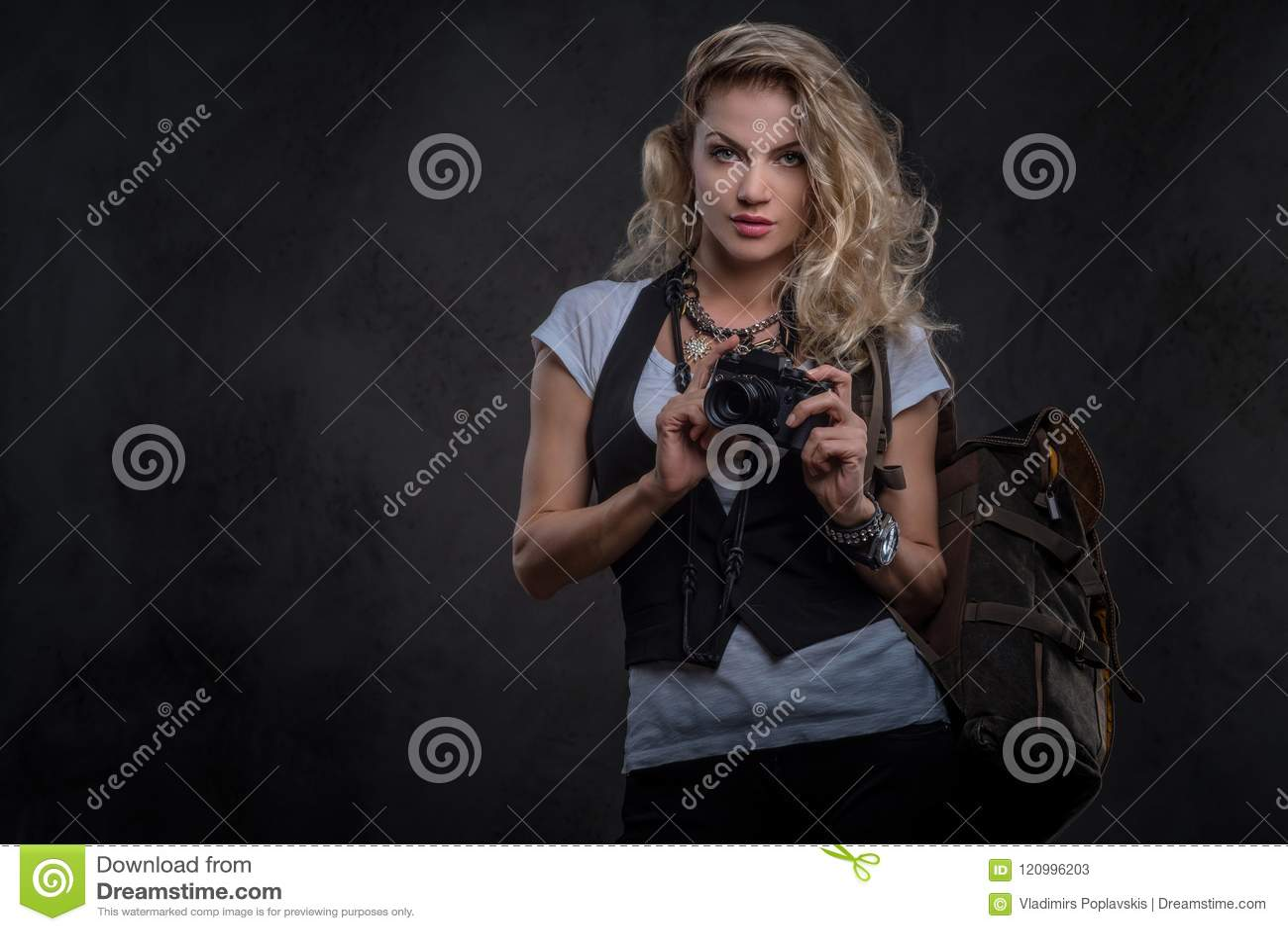 Het charmeren van krullend blondewijfje gekleed in een wit t-shirt en een vest draagt heel wat toebehoren en polshorloge, het ste