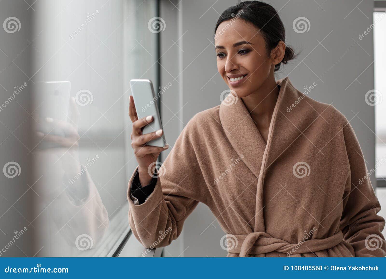 Het charmeren van vrolijke vrouw gebruikt haar smartphone