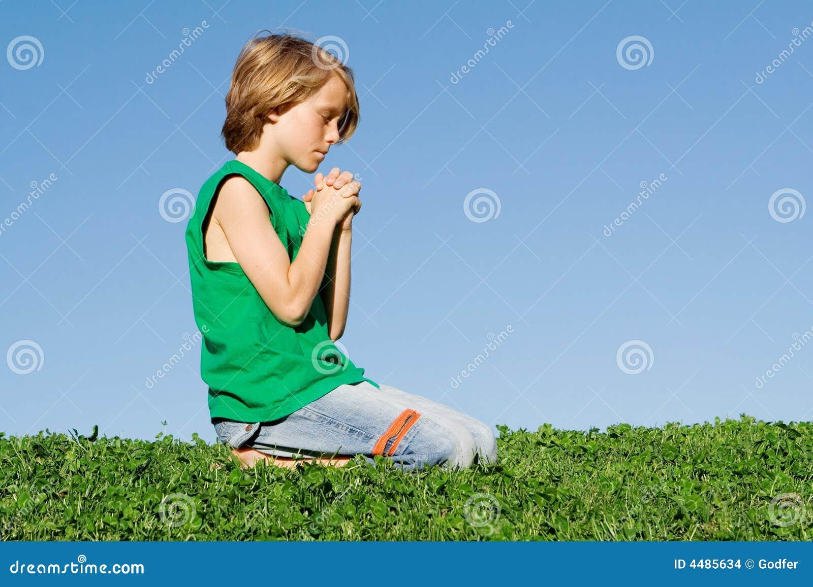 Het christelijke kind het knielen bidden