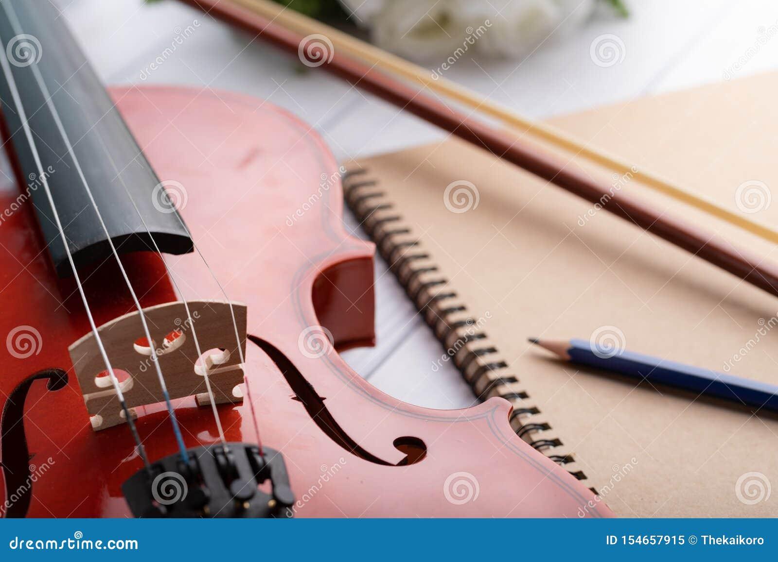 Het close-up schoot vioolorkest instrumentaal over witte houten achtergrond ondiepe velddiepte uitgezochte nadruk