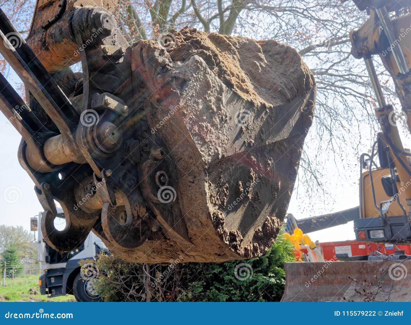 Het close-up van een grote graafwerktuigschop vulde met een machtige lading van los bruin zand bij de bouwwerf
