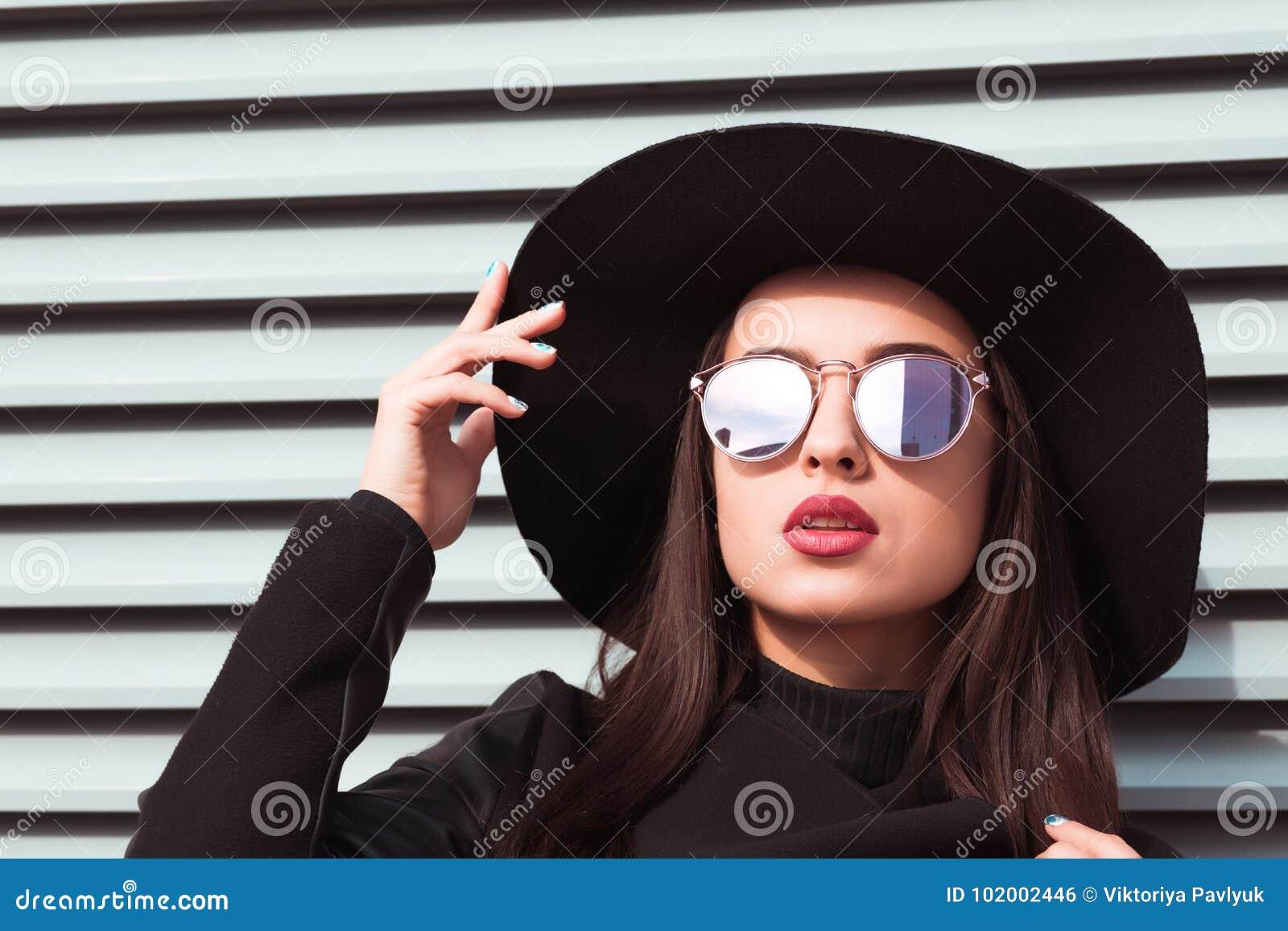 Het close-upportret van jong verleidelijk model draagt hoed en sunglass