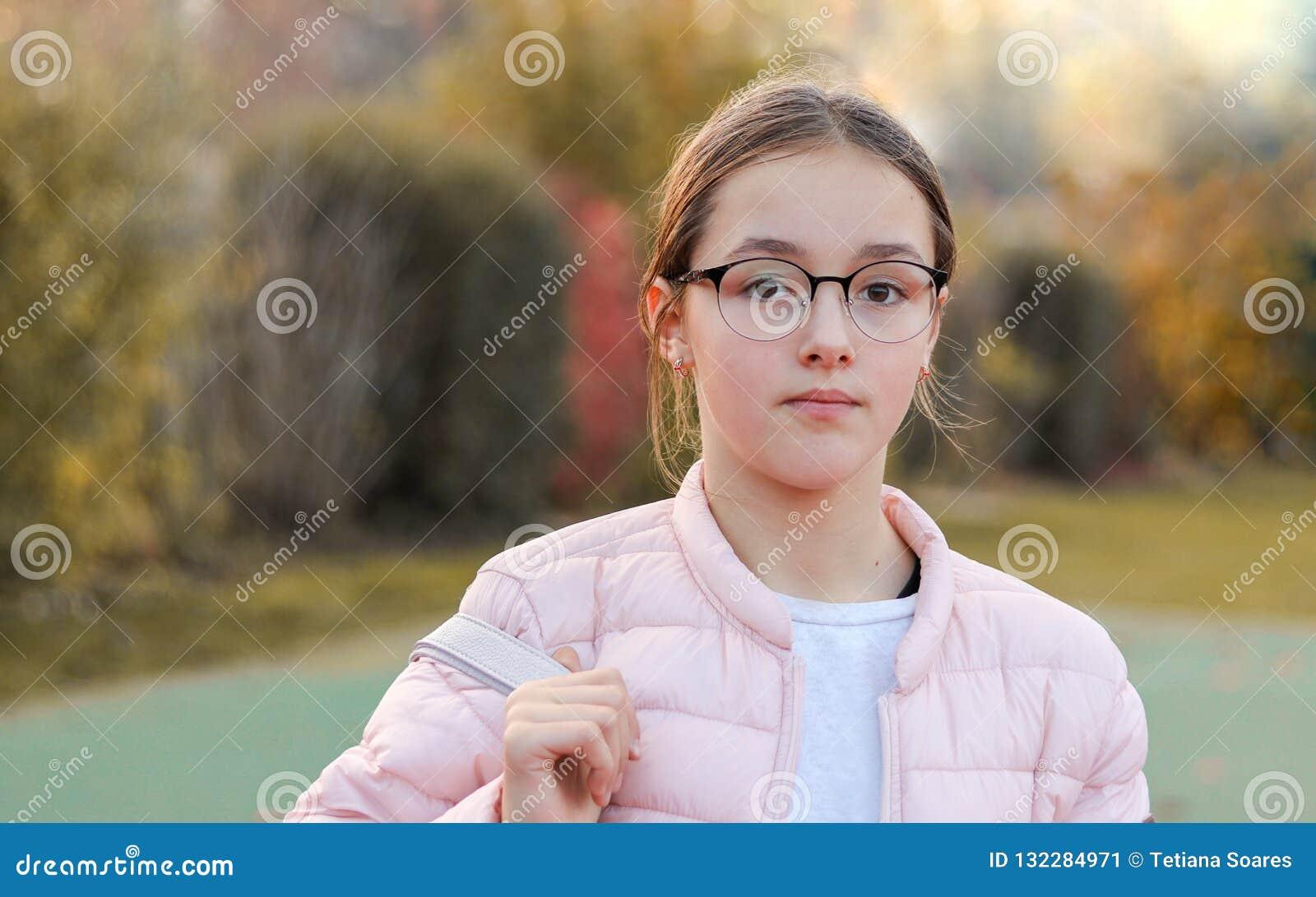 Het close-upportret van mooi preteen meisje in manierglazen met ernstige gezichtsuitdrukking buiten in de herfstpark