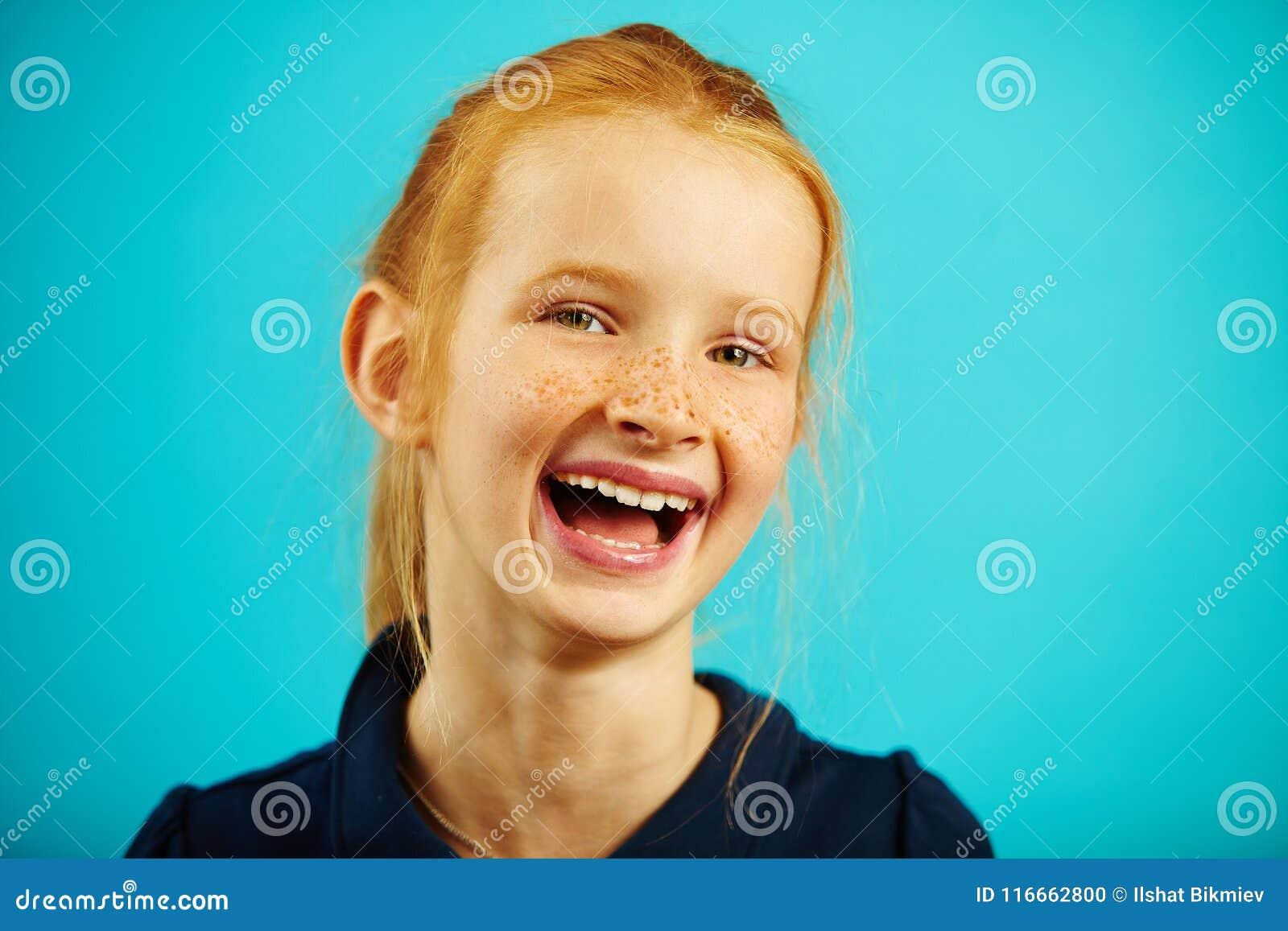 Het close-upportret van vrolijk lachend meisje met rood haar en sproeten op blauw isoleerde achtergrond Gelukkig Kind