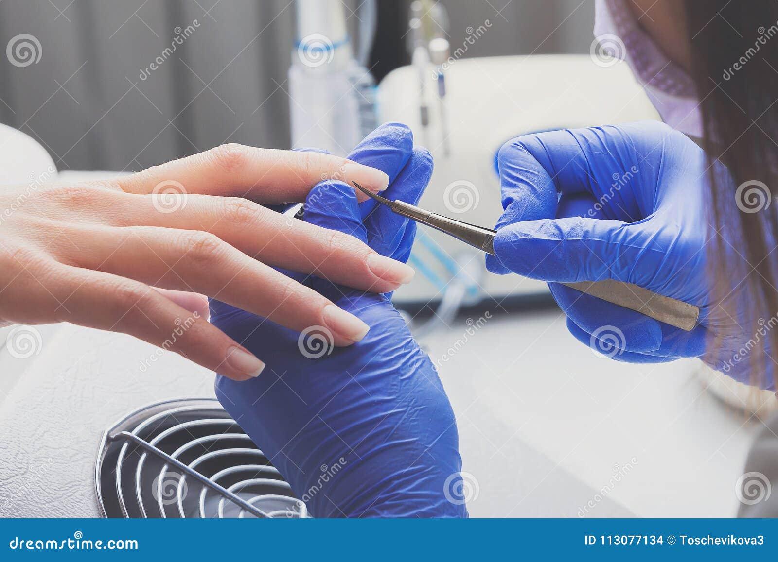 Het close-upschot van manicure in blauwe rubberhandschoenen en medisch masker verwijdert opperhuid op vrouwelijke spijkers gebrui