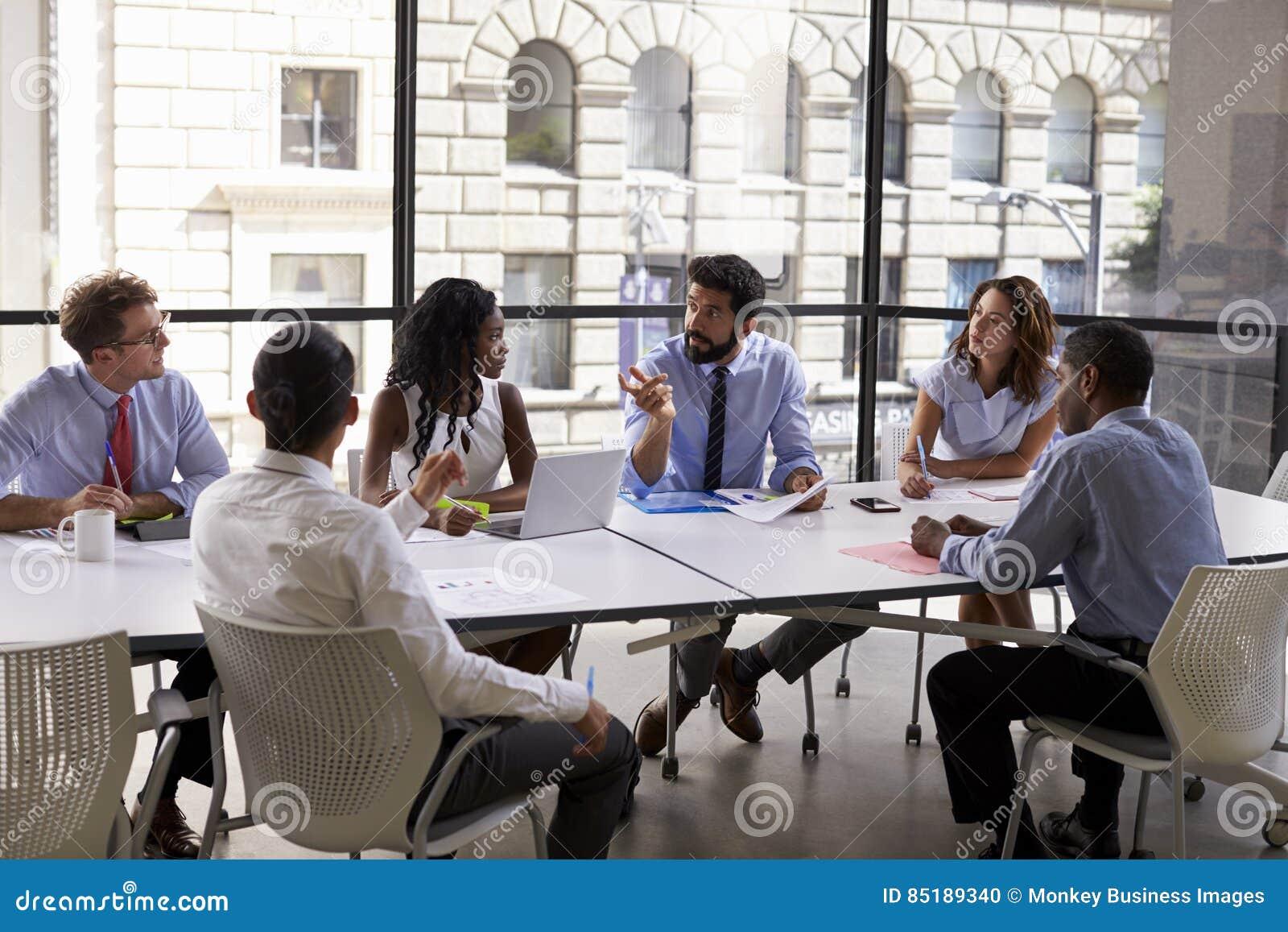 Het collectieve bedrijfsteam en de manager in een vergadering, sluit omhoog
