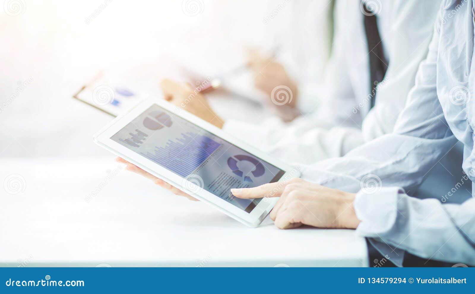 Het commerciële team die digitale tablet gebruiken voert analyse van marketing grafiek uit