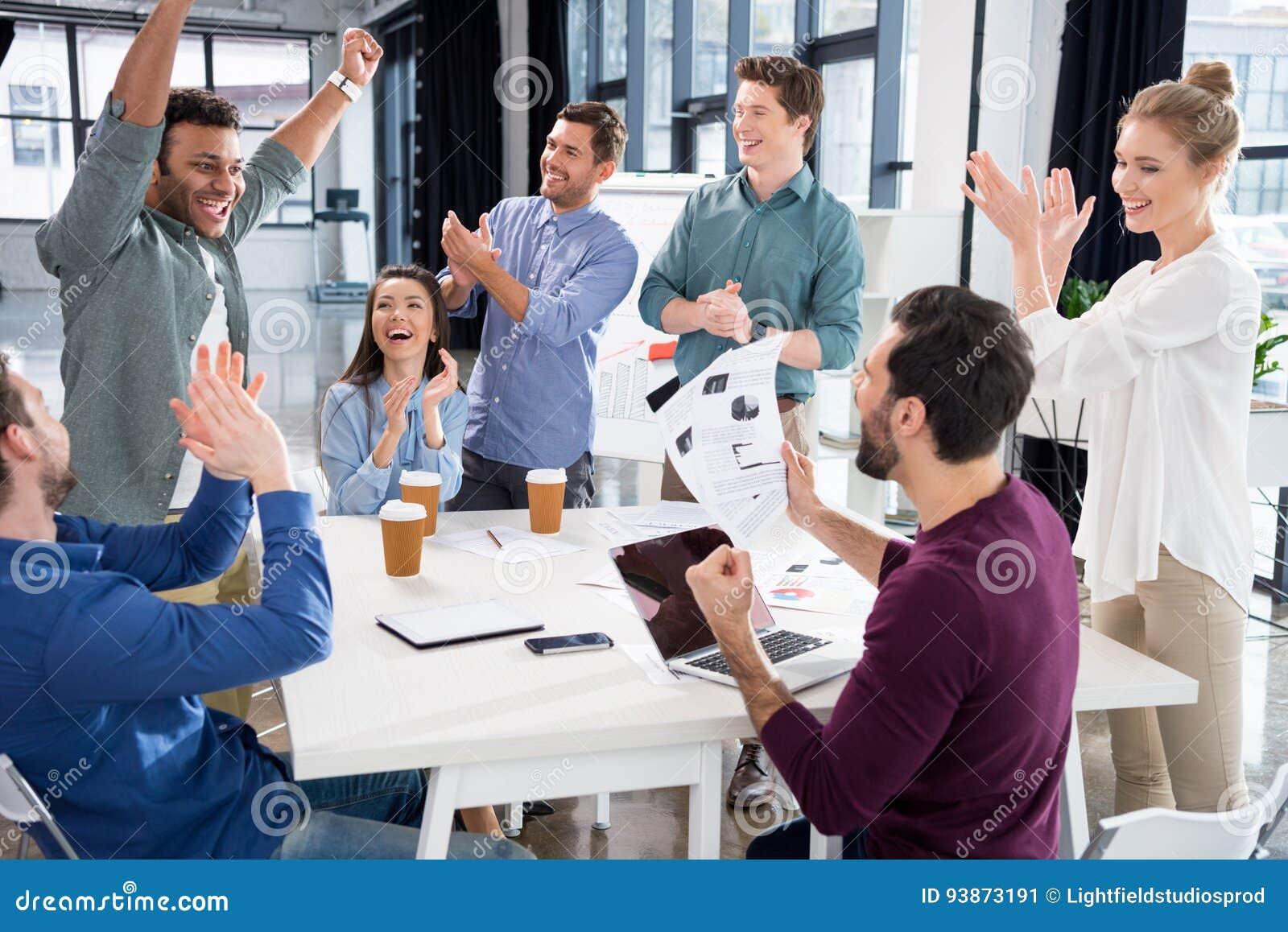 Het commerciële team vieren succes samen op werkplaats in bureau