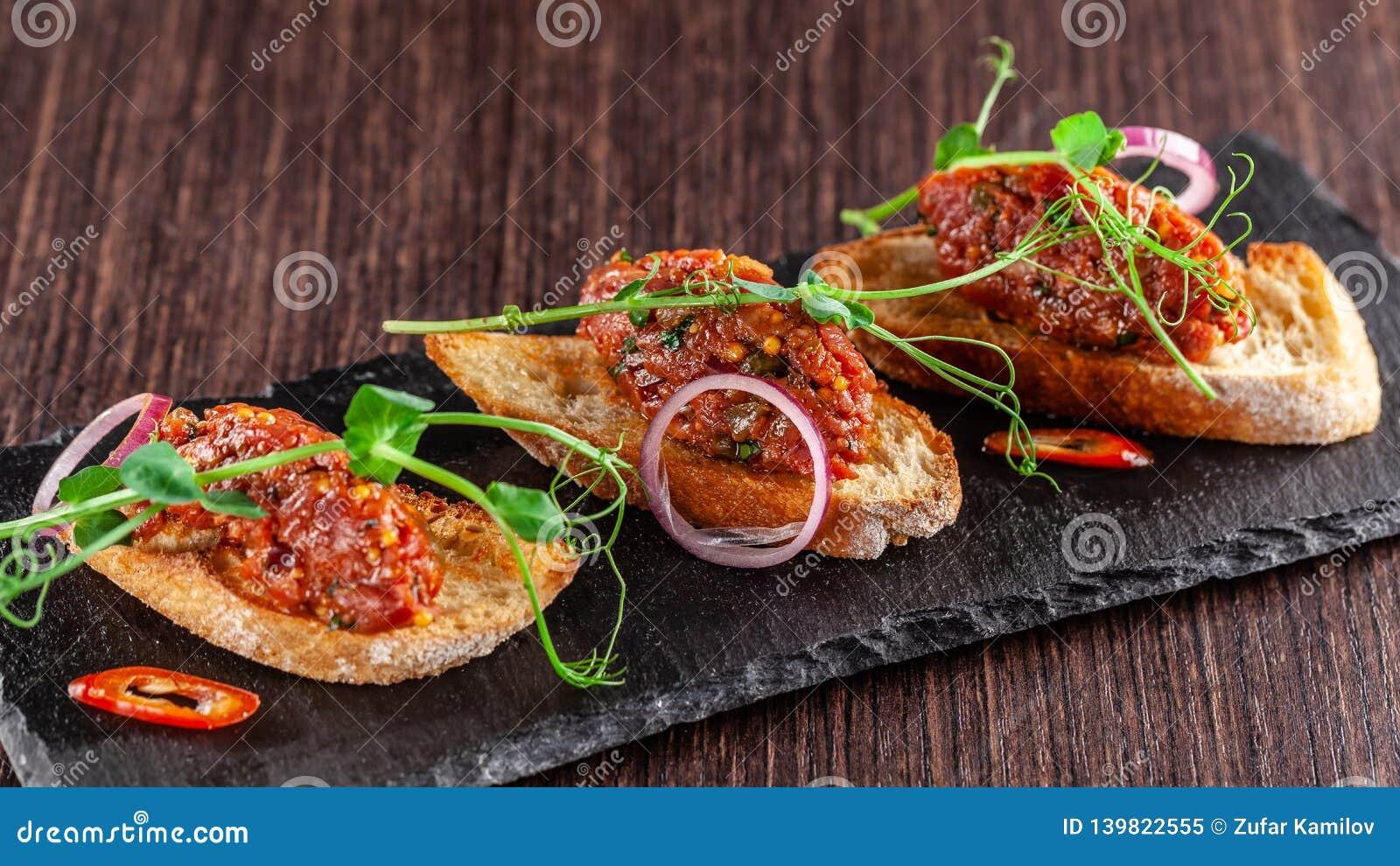 Het concept Mexicaanse keuken Rundvlees tartare met peterselie, Franse mosterdbonen op baguettecroutons Een schotel in het restau