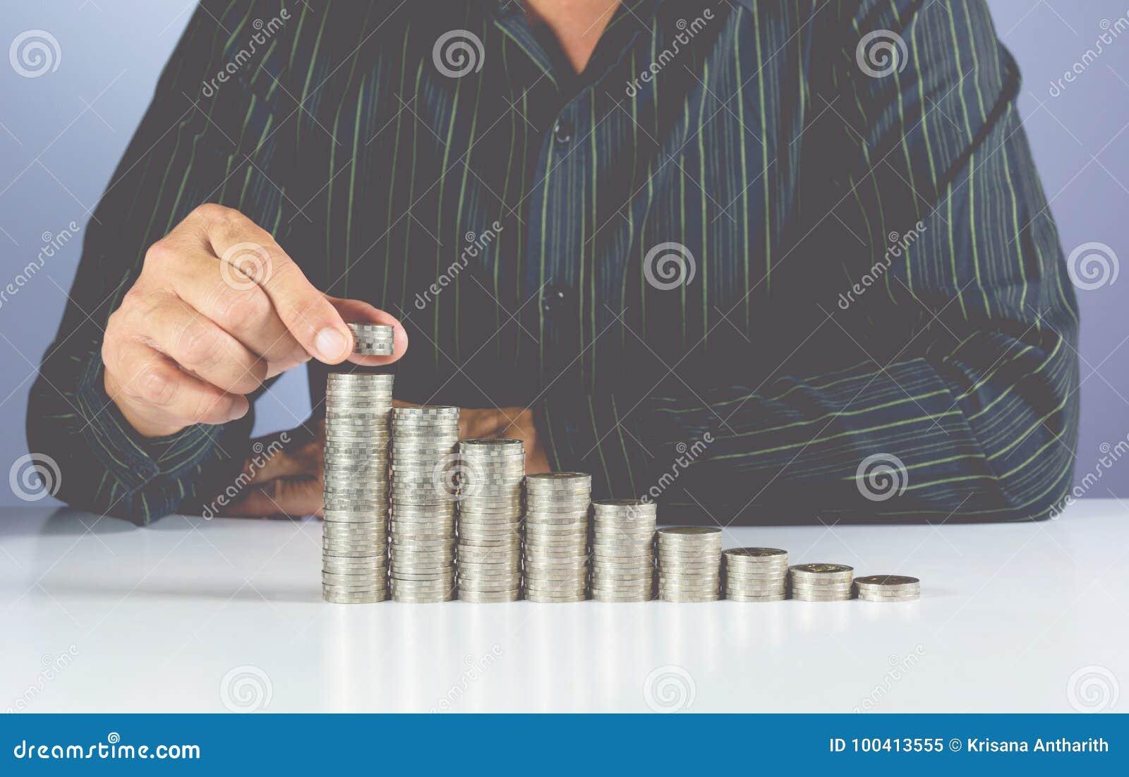 Het concept van het besparingsgeld en hand van zakenman die geldmuntstuk zetten