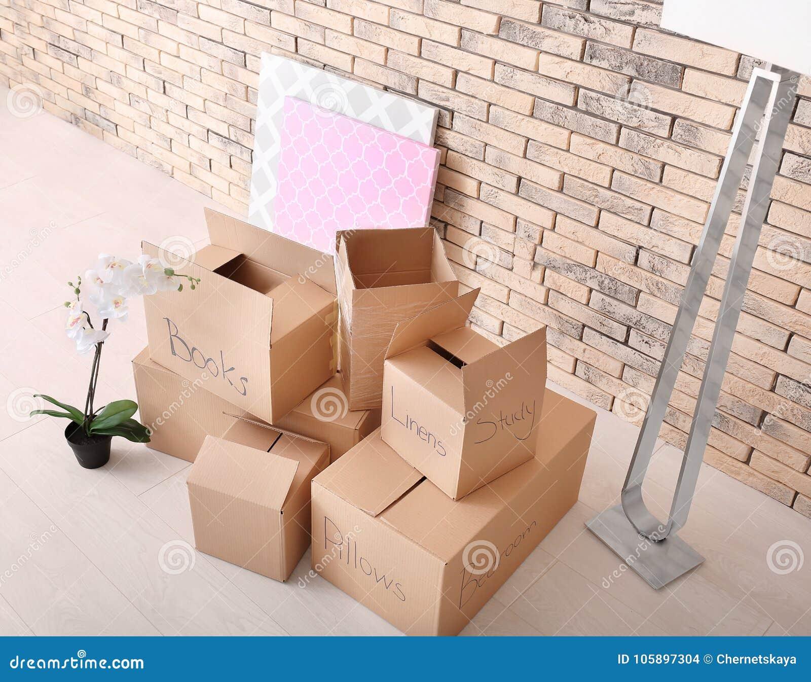 Het concept van het bewegingshuis Kartondozen op vloer