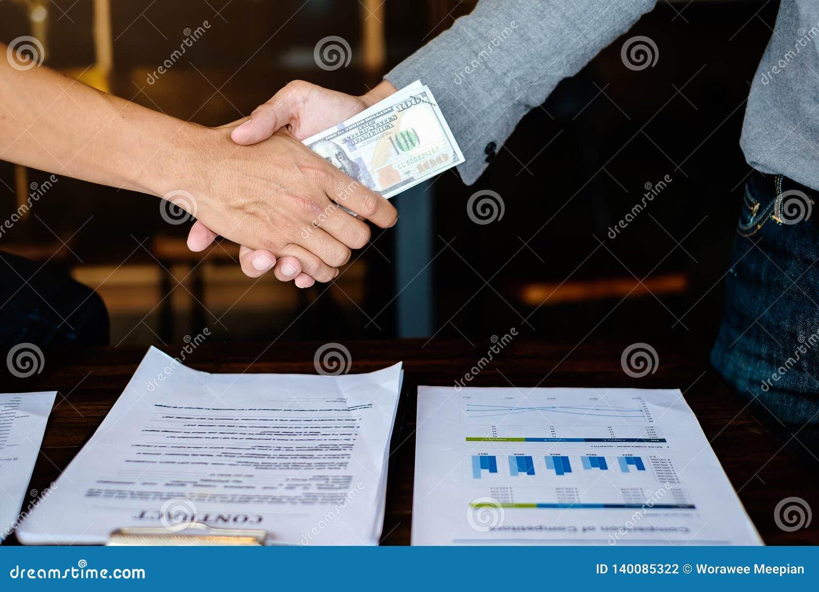 Het concept van de bedrijfsvennootschapvergadering Beeld businessmans handenschudden met geld Corruptie en Antiomkoperij