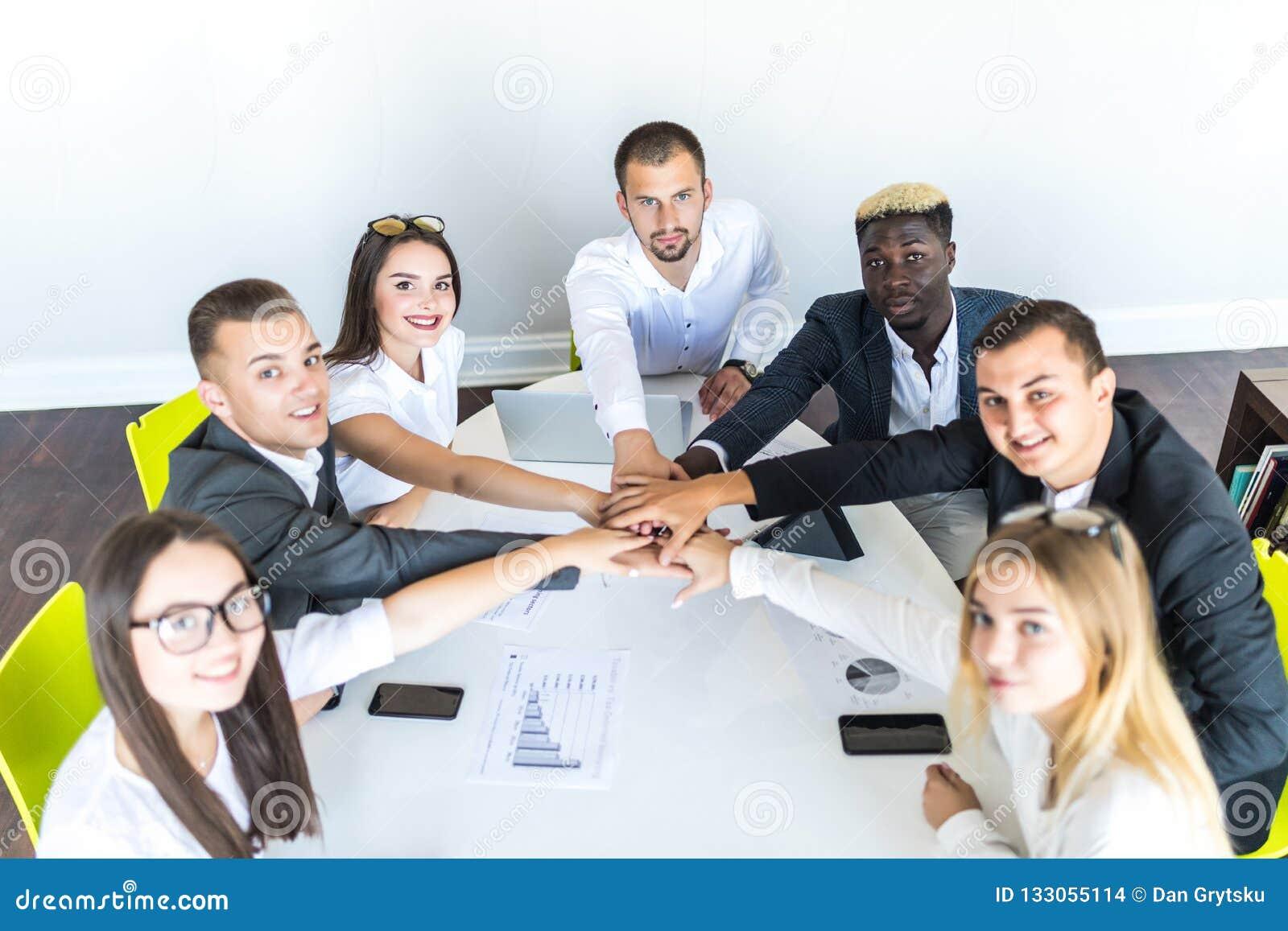 Het concept van de eenheid Close-up van multi etnische mensen die handen houden samen terwijl het rondhangen van het bureau